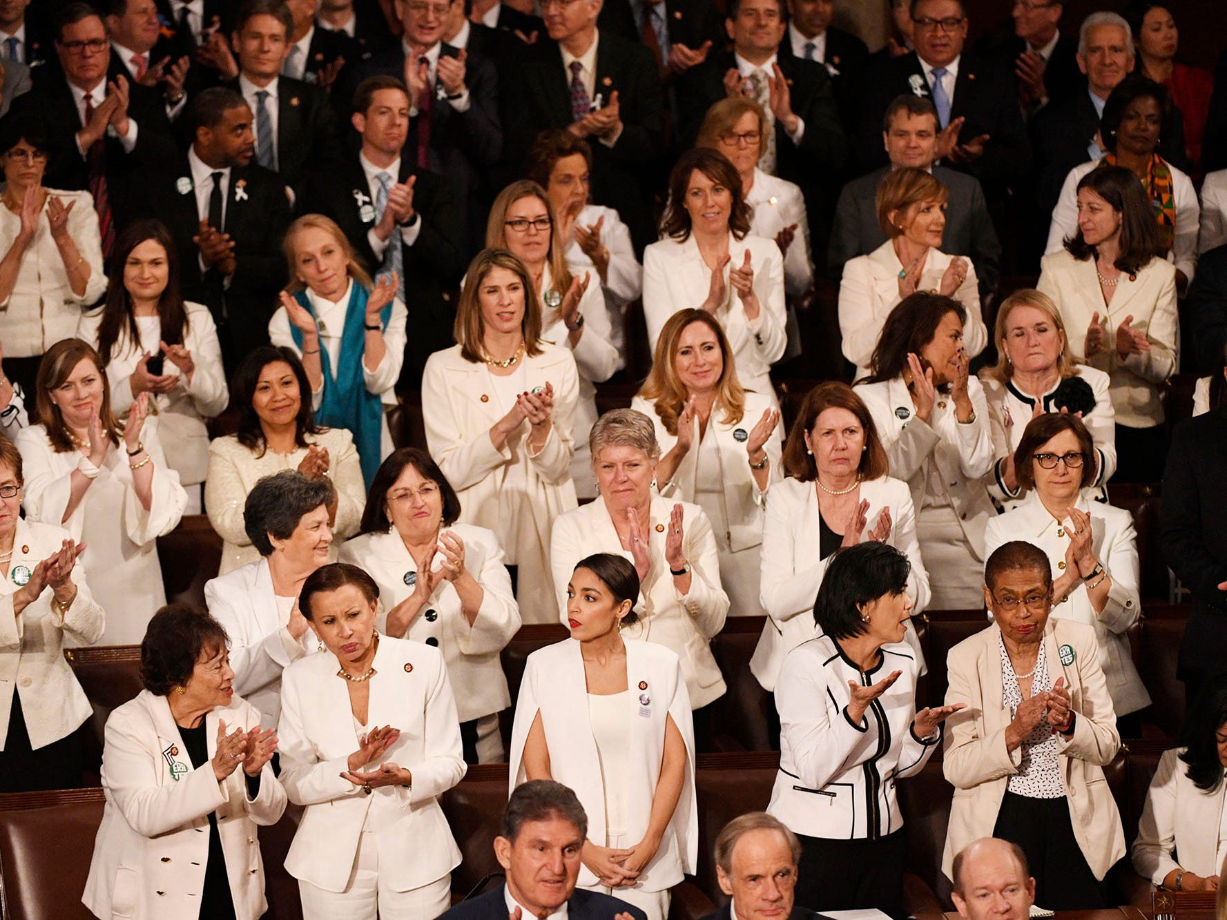 Congresswomen are recognized by President Donald Trump as he delivers the State of the Union address. The white color choice they wear is meant to honor the women's suffrage movement that led to the ratification of the 19th Amendment in 1920.