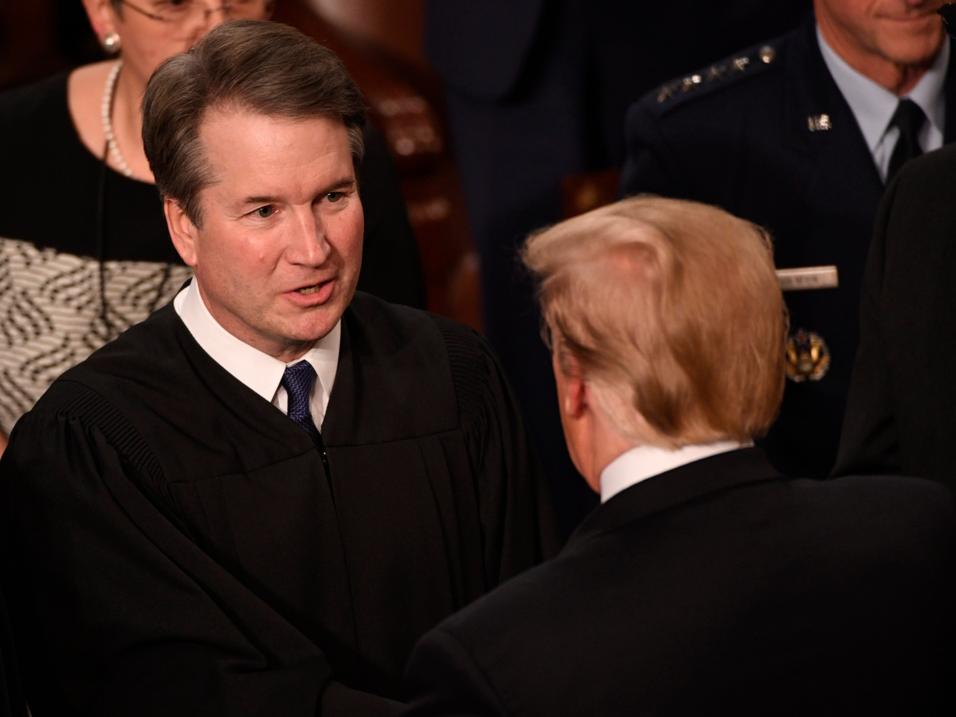 Justice Brett Kavanaugh greets President Donald Trump before he delivers the State of the Union address.