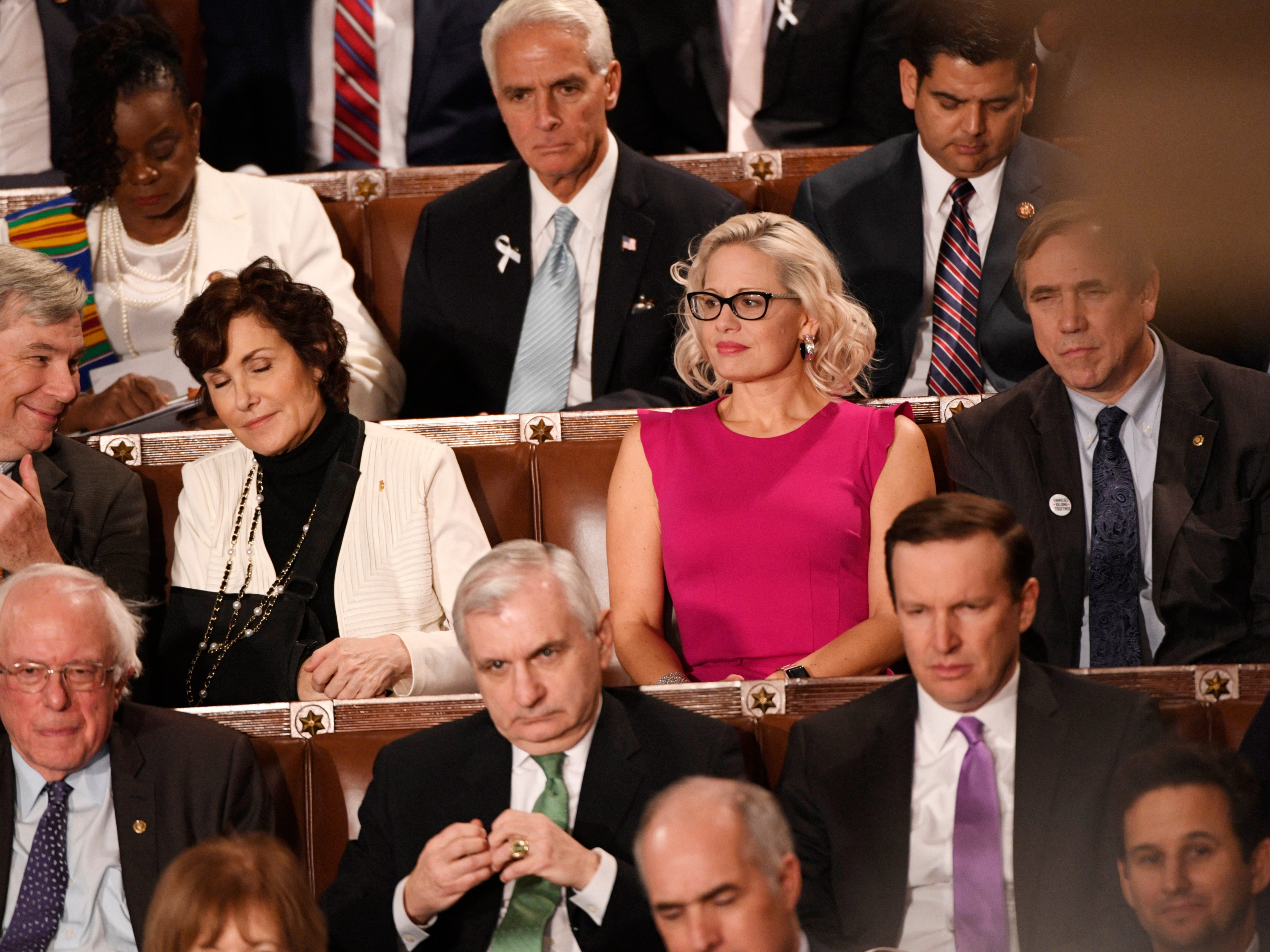 Sen. Kyrsten Sinema (D-Ariz) listens to President Donald Trump delivers the State of the Union address.