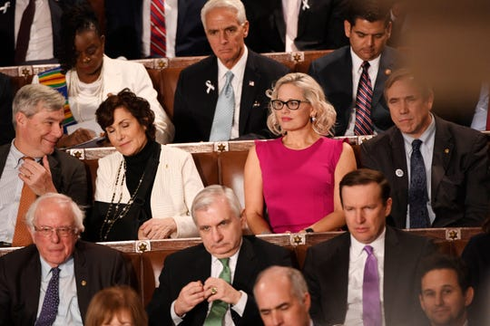 Sen. Kyrsten Sinema, D-Ariz., center, listens to President Donald Trump deliver his State of the Union address in the U.S. Capitol in Washington, D.C., Feb. 5, 2019.