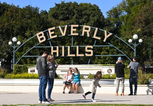 """Tourists gather to take snapshots in front of the """"Beverly Hills"""" sign in Beverly Gardens Park near Rodeo Drive."""