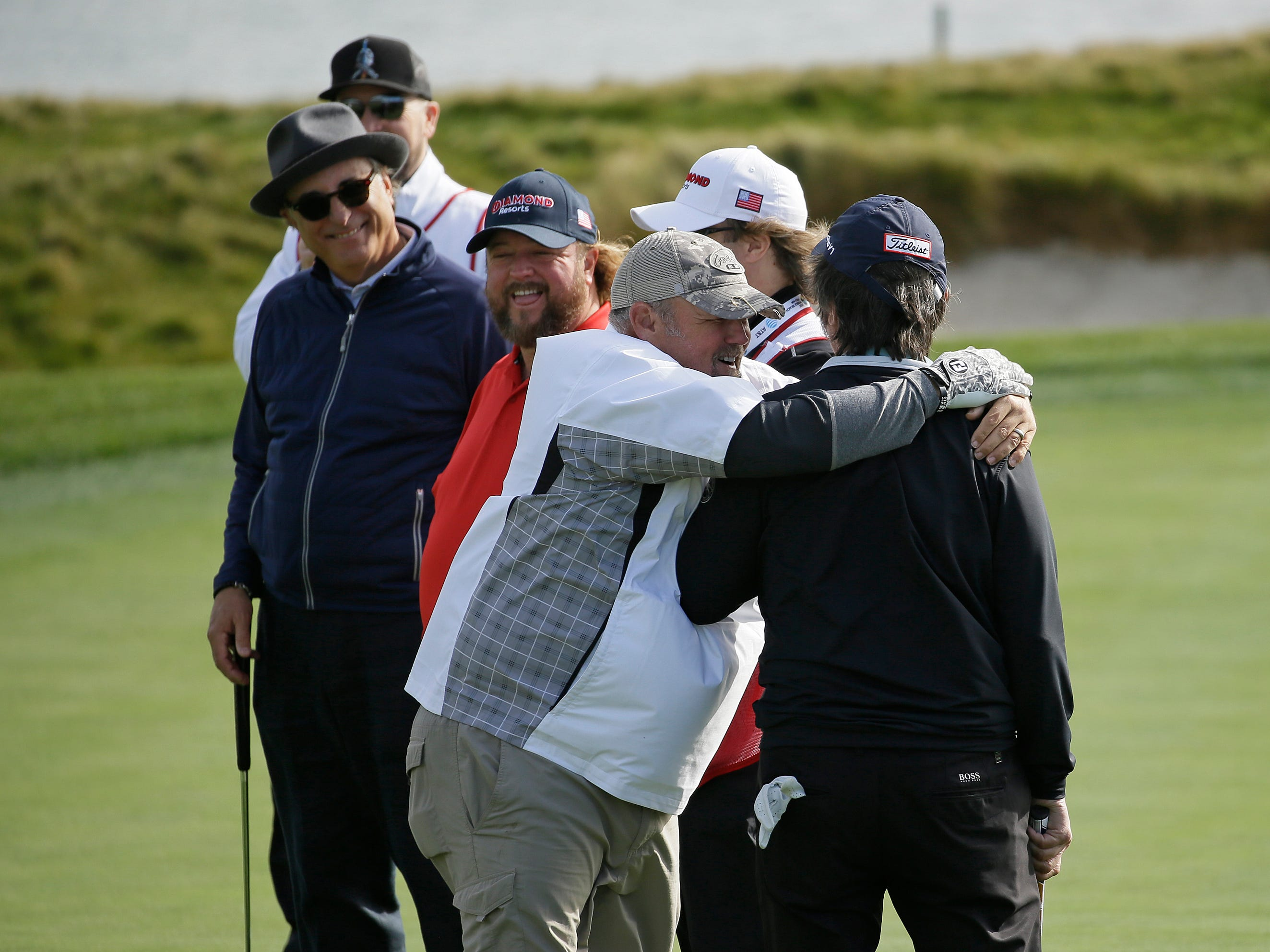Ray Romano is embraced by Daniel Lawrence Whitney, known professionally as Larry the Cable Guy on the 17th green alongside singer Colt Ford and actor Andy Garcia during the celebrity challenge event of the AT&T Pebble Beach National Pro-Am.