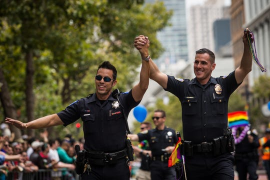 Sacramento Police Officer Jeff Kuhlmann, left, marches with his boyfriend, Los Angeles Police Officer David Ayala, right, in the San Francisco Gay Pride Parade, June 28, 2015 in San Francisco, California.
