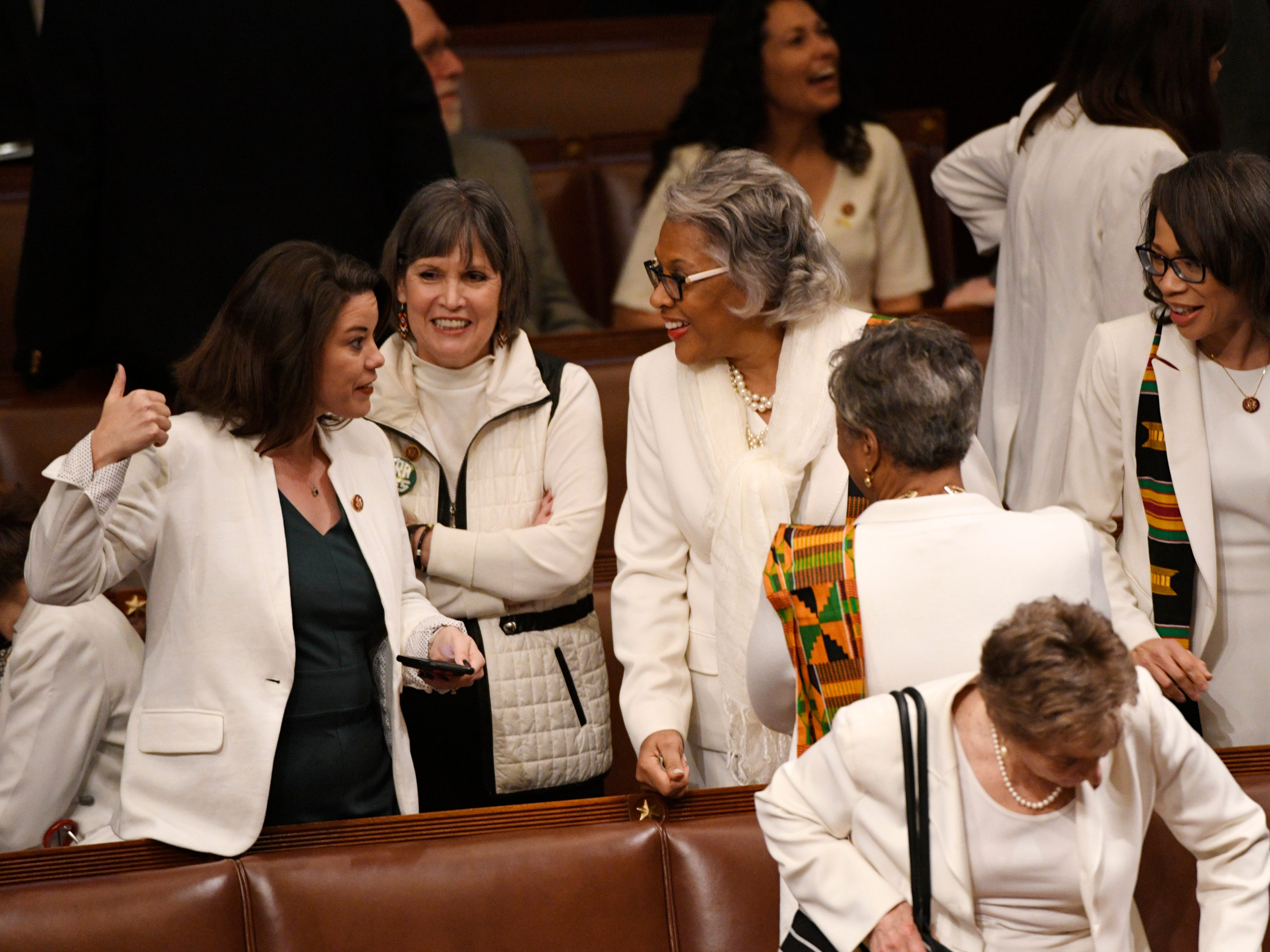 Women members of Congress dressed in white gather prior to President Donald Trump delivering the State of the Union address, Feb. 5, 2019.