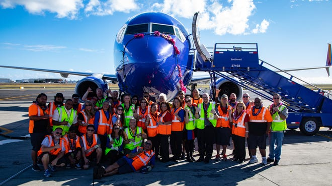 A Southwest Airlines Boeing 737-800 is seen in Honolulu with celebrating employees after the carrier's first-ever touchdown in the Hawaiian Islands on Feb. 5, 2019. The flight was part of a certification effort needed to begin passenger service.