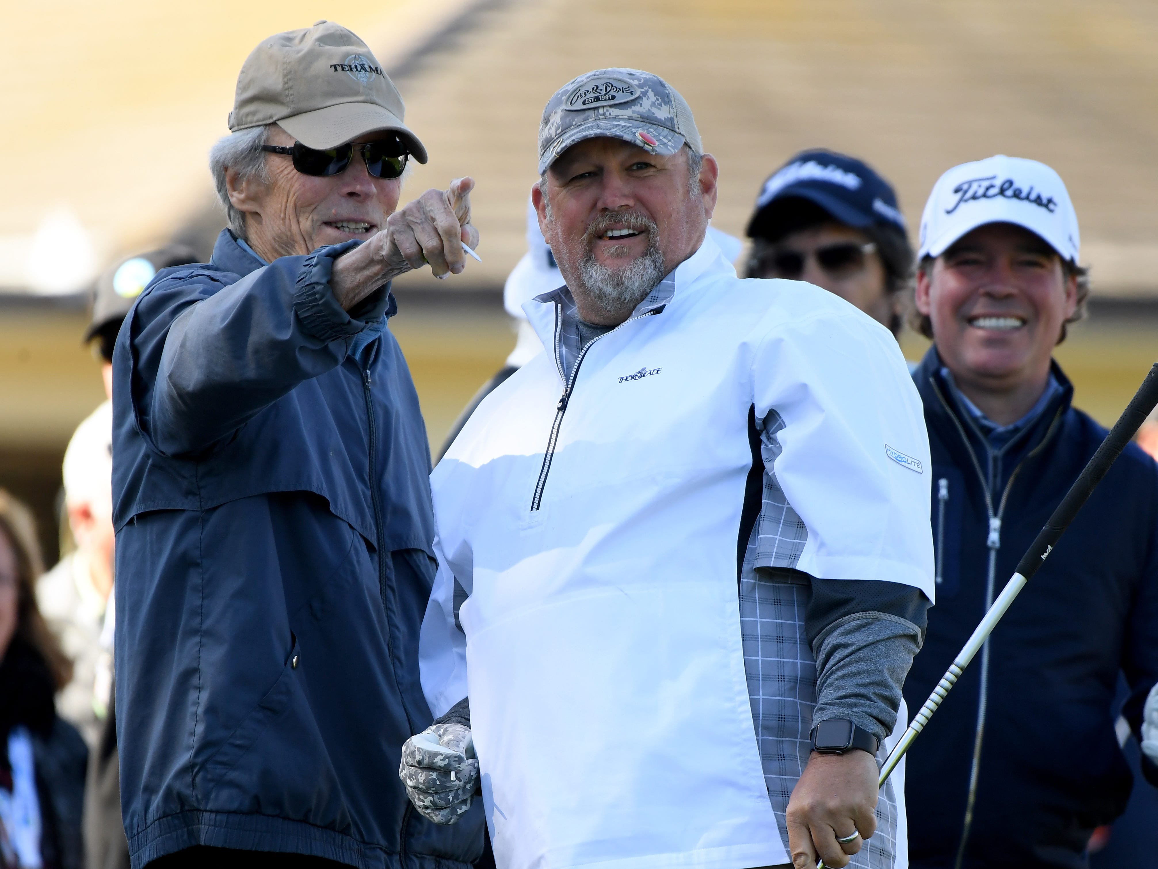 Clint Eastwood, and Daniel Lawrence Whitney aka Larry the Cable Guy react to a shot on the fist hole during the 3M Celebrity Challenge at the AT&T Pebble Beach Pro-Am.