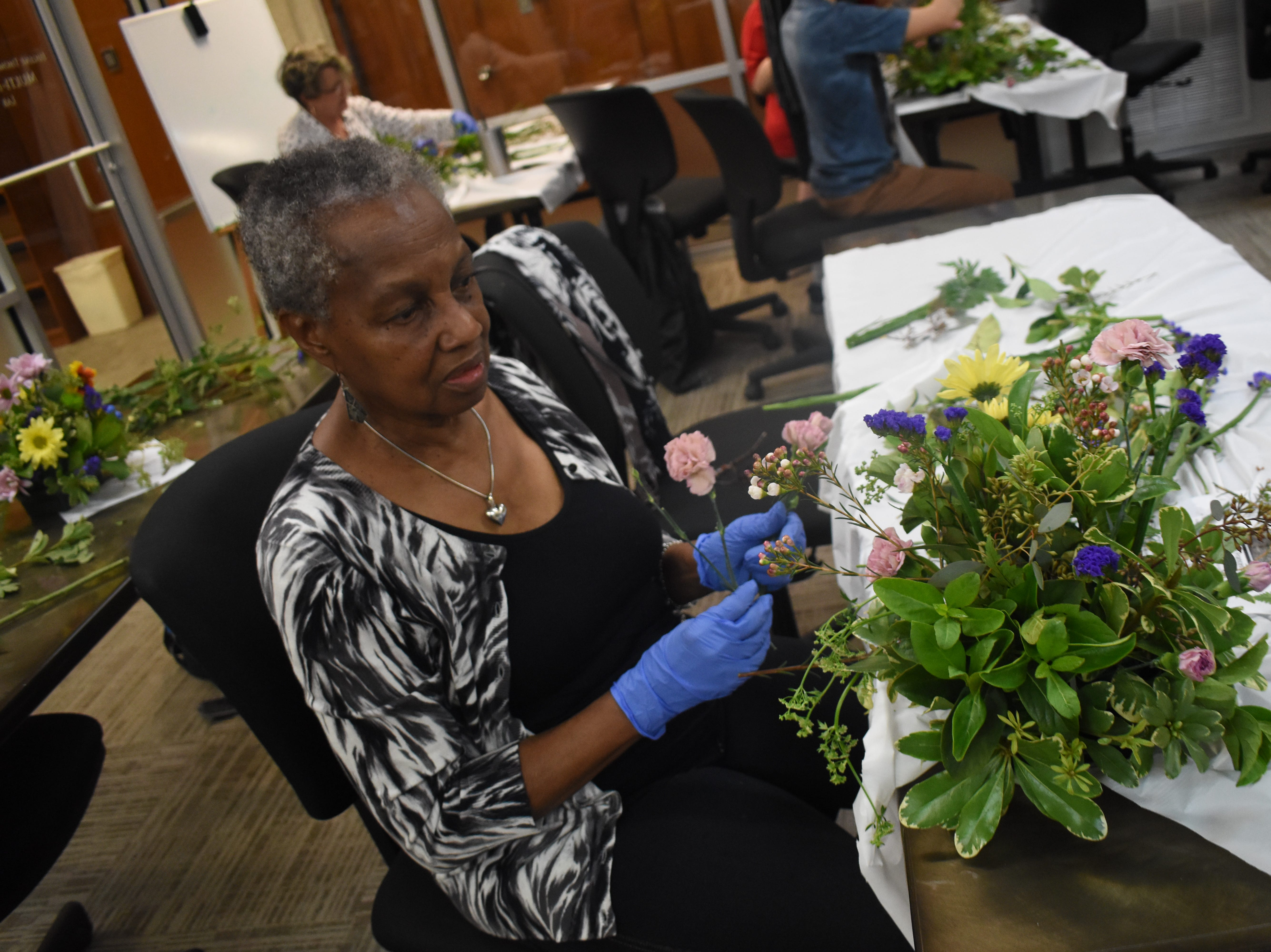 "Jean Clayton works on her flower arrangement in a flower arranging class, ""Flowers For Your Sweetheart,"" taught by Frances Boudreaux, a licensed florist, at the Main Library of the Rapides Parish Library Wednesday, Feb. 6, 2019. Some of the tips Boudreaux told participants was to try various foliage to see what works best for them. She recommended cutting garden flowers in the morning when flowers are full of moisture and the are is cooler. Flowers such as roses, iris, gladioli can be cut as buds and may open later. Marigolds, delphiniums and dianthus or sweet William, must be cut with they are open. Some of the common foliage that were used in the arrangements that can be found in Central Louisiana are pittosporum, either variegated or solid green; baker's fern or leather leaf; sweet viburnum, sweet olive, rosemary, ginger, evergreen boughs, holly, aspidistra or iron plant, and herbs such as rosemary, lavender, mint, basil and lemon balm. 