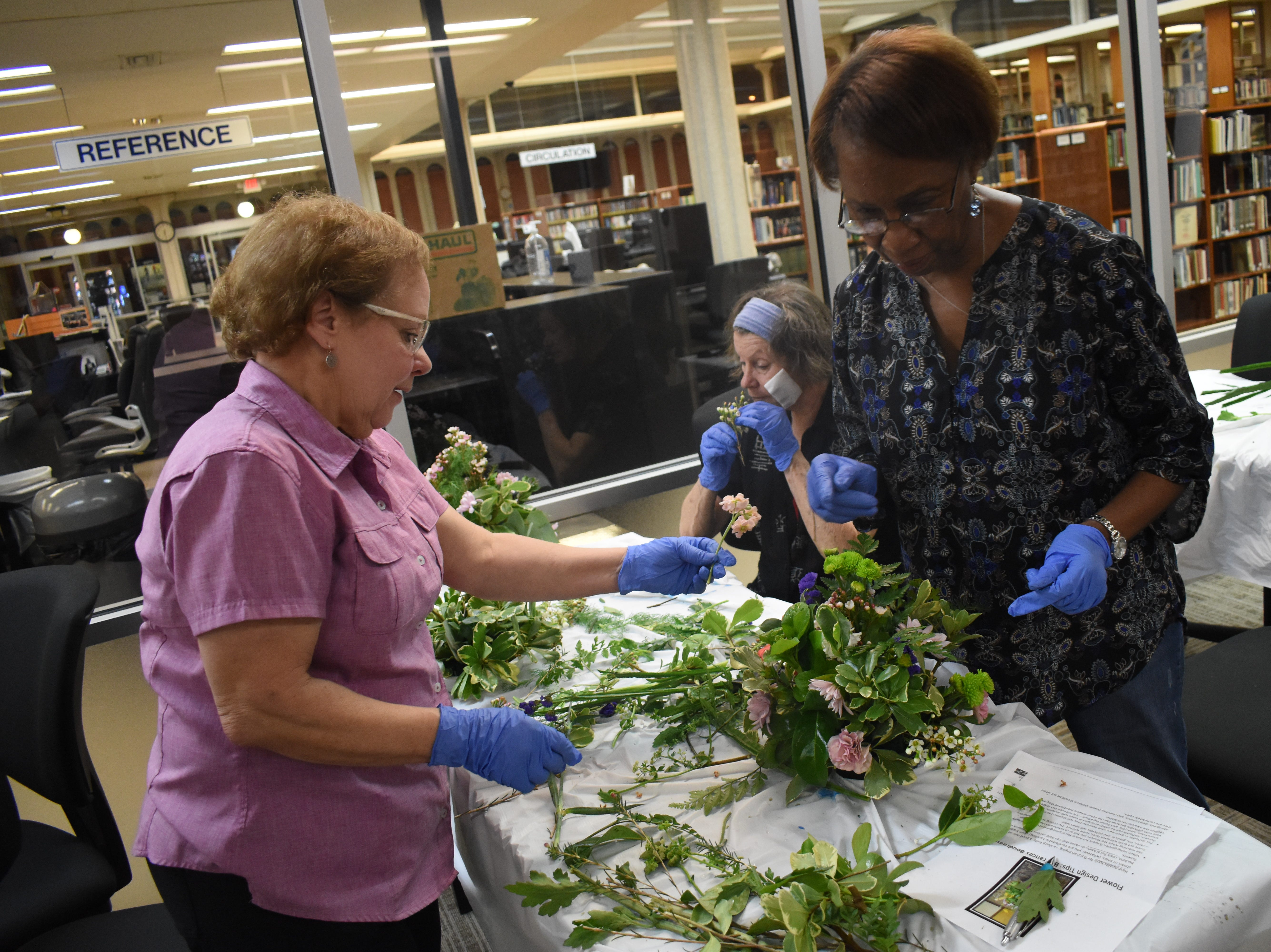 "Frances Boudreaux (left), a licensed florist, helps Ameil Washington as she makes a flower arrangement in a class, ""Flowers For Your Sweetheart,"" taught by Boudreaux at the Main Library of the Rapides Parish Library Wednesday, Feb. 6, 2019. Some of the tips Boudreaux told participants was to try various foliage to see what works best for them. She recommended cutting garden flowers in the morning when flowers are full of moisture and the are is cooler. Flowers such as roses, iris, gladioli can be cut as buds and may open later. Marigolds, delphiniums and dianthus or sweet William, must be cut with they are open. Some of the common foliage that were used in the arrangements that can be found in Central Louisiana are pittosporum, either variegated or solid green; baker's fern or leather leaf; sweet viburnum, sweet olive, rosemary, ginger, evergreen boughs, holly, aspidistra or iron plant, and herbs such as rosemary, lavender, mint, basil and lemon balm. 