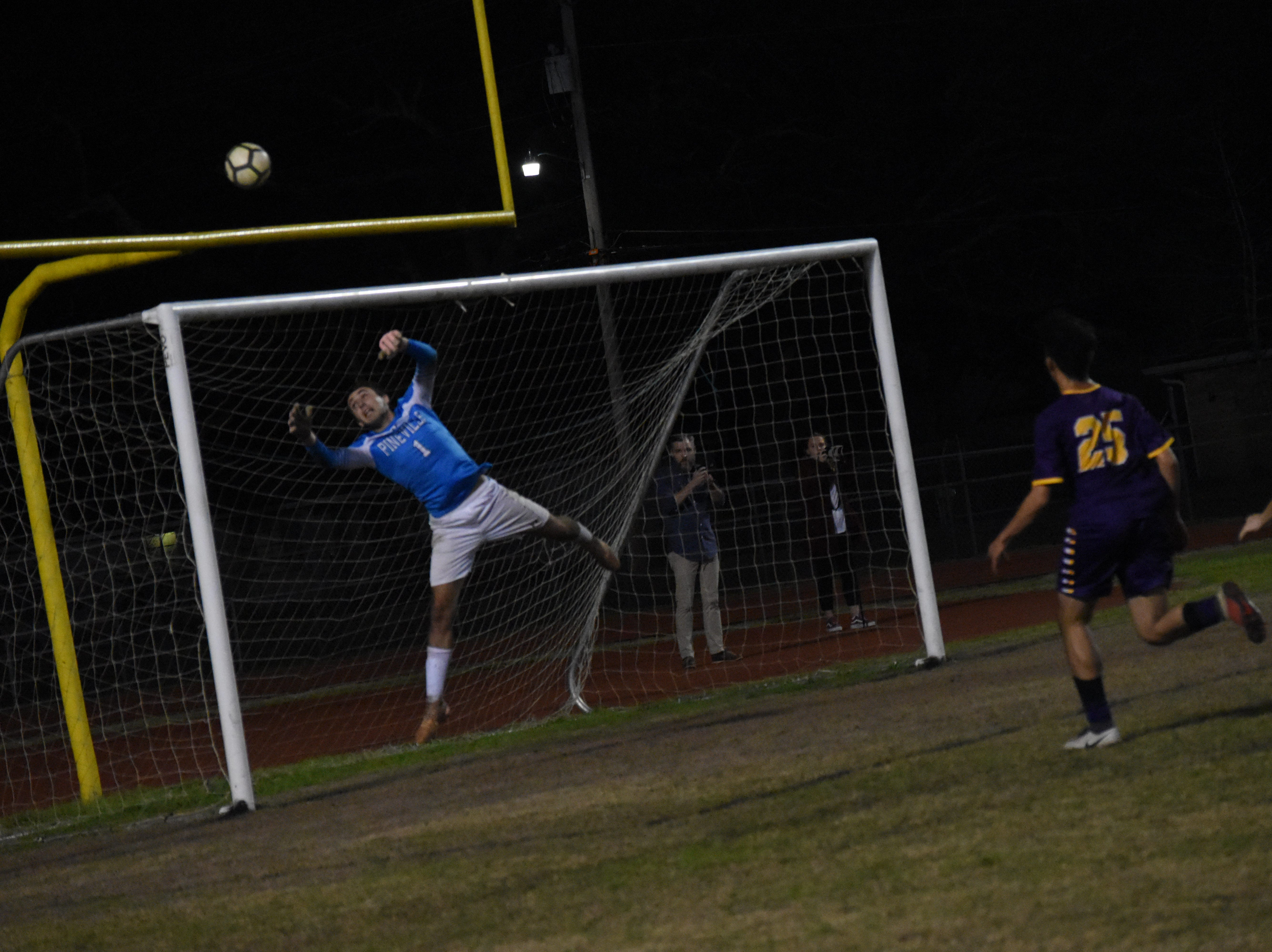 Pineville High School goalkeeper Brandon Cespiva (1) reaches up for a save against Alexandria Senior High in the Division I regionals held Wednesday, Feb. 6, 2019. ASH won 4-3 in penalty kicks.