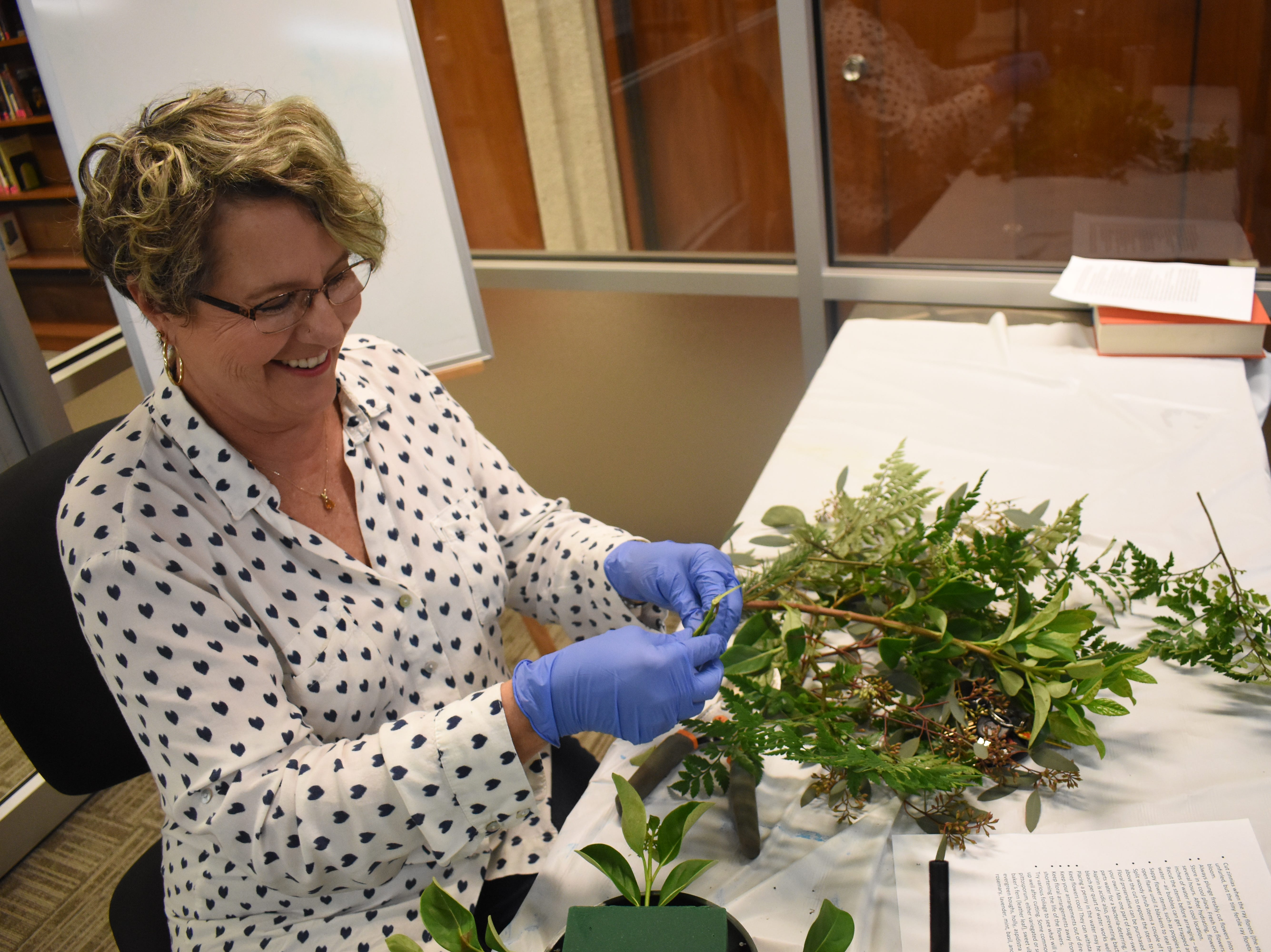 "Sonia Chevallier works on a floral arrangement in a class, ""Flowers For Your Sweetheart"" taught by Frances Boudreaux, a licensed florist, at the Main Library of the Rapides Parish Library Wednesday, Feb. 6, 2019. Some of the tips Boudreaux told participants was to try various foliage to see what works best for them. She recommended cutting garden flowers in the morning when flowers are full of moisture and the are is cooler. Flowers such as roses, iris, gladioli can be cut as buds and may open later. Marigolds, delphiniums and dianthus or sweet William, must be cut with they are open. Some of the common foliage that were used in the arrangements that can be found in Central Louisiana are pittosporum, either variegated or solid green; baker's fern or leather leaf; sweet viburnum, sweet olive, rosemary, ginger, evergreen boughs, holly, aspidistra or iron plant, and herbs such as rosemary, lavender, mint, basil and lemon balm. 