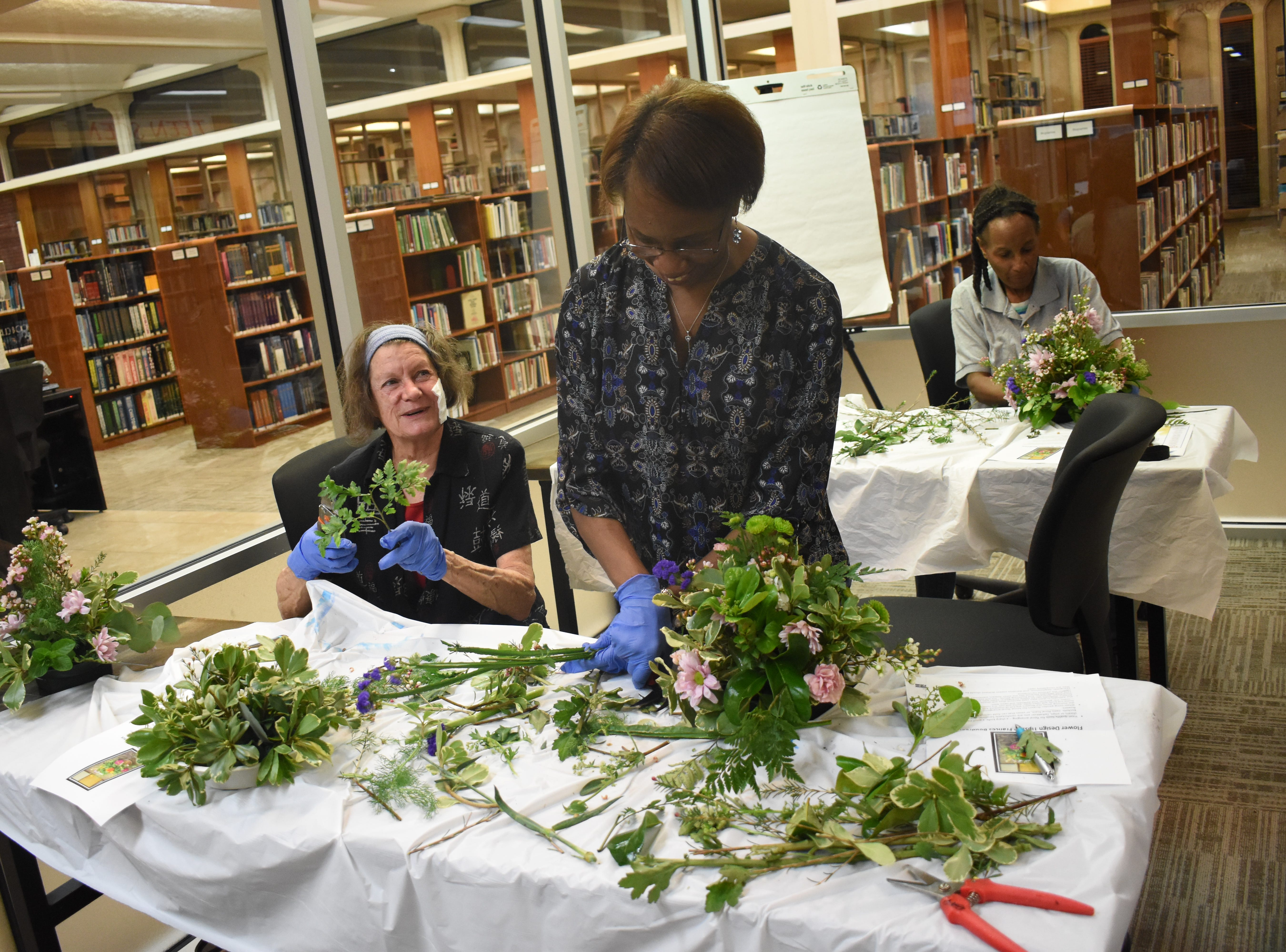 "Pam Glass (left) and Ameli Washington work on flower arraignments in a class ""Flowers For Your Sweetheart,"" taught by Frances Boudreaux, a licensed florist, at the Main Library of the Rapides Parish Library Wednesday, Feb. 6, 2019. Some of the tips Boudreaux told participants was to try various foliage to see what works best for them. She recommended cutting garden flowers in the morning when flowers are full of moisture and the are is cooler. Flowers such as roses, iris, gladioli can be cut as buds and may open later. Marigolds, delphiniums and dianthus or sweet William, must be cut with they are open. Some of the common foliage that were used in the arrangements that can be found in Central Louisiana are pittosporum, either variegated or solid green; baker's fern or leather leaf; sweet viburnum, sweet olive, rosemary, ginger, evergreen boughs, holly, aspidistra or iron plant, and herbs such as rosemary, lavender, mint, basil and lemon balm. 