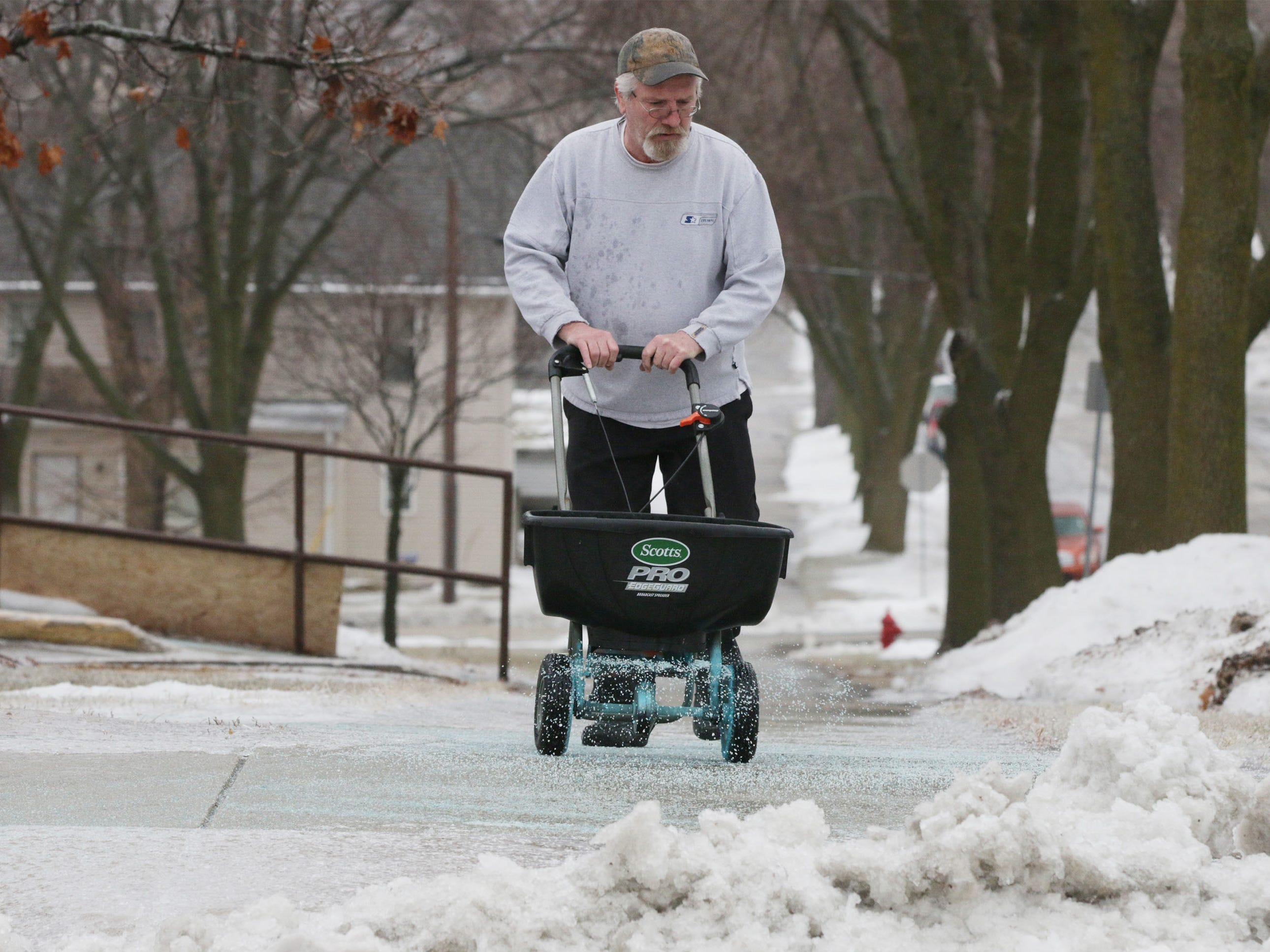 "Chuck McDonell, who maintains sidewalks at Park Plaza housing on North 9th Street, spreads salt, Tuesday, February 5, 2019, in Sheboygan, Wis. McDonell said, ""This is already my fourth time salting today."""