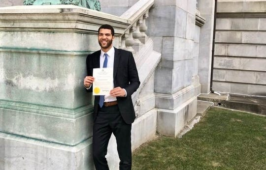 Braeden Anderson holds up his degree from Seton Hall Law