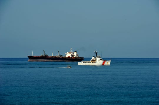U.S. Coast Guard Cutter Reliance and a commercial vessel as the two ships transit into and out of Naval Station Guantanamo Bay, Cuba on July, 19, 2017.