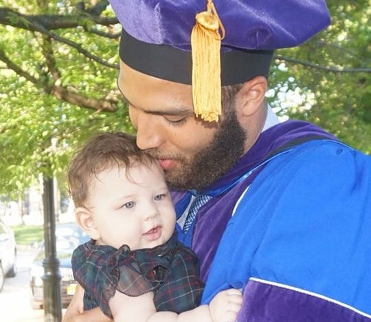 Braeden Anderson, after his Seton Hall Law graduation, embraces daughter Arden.