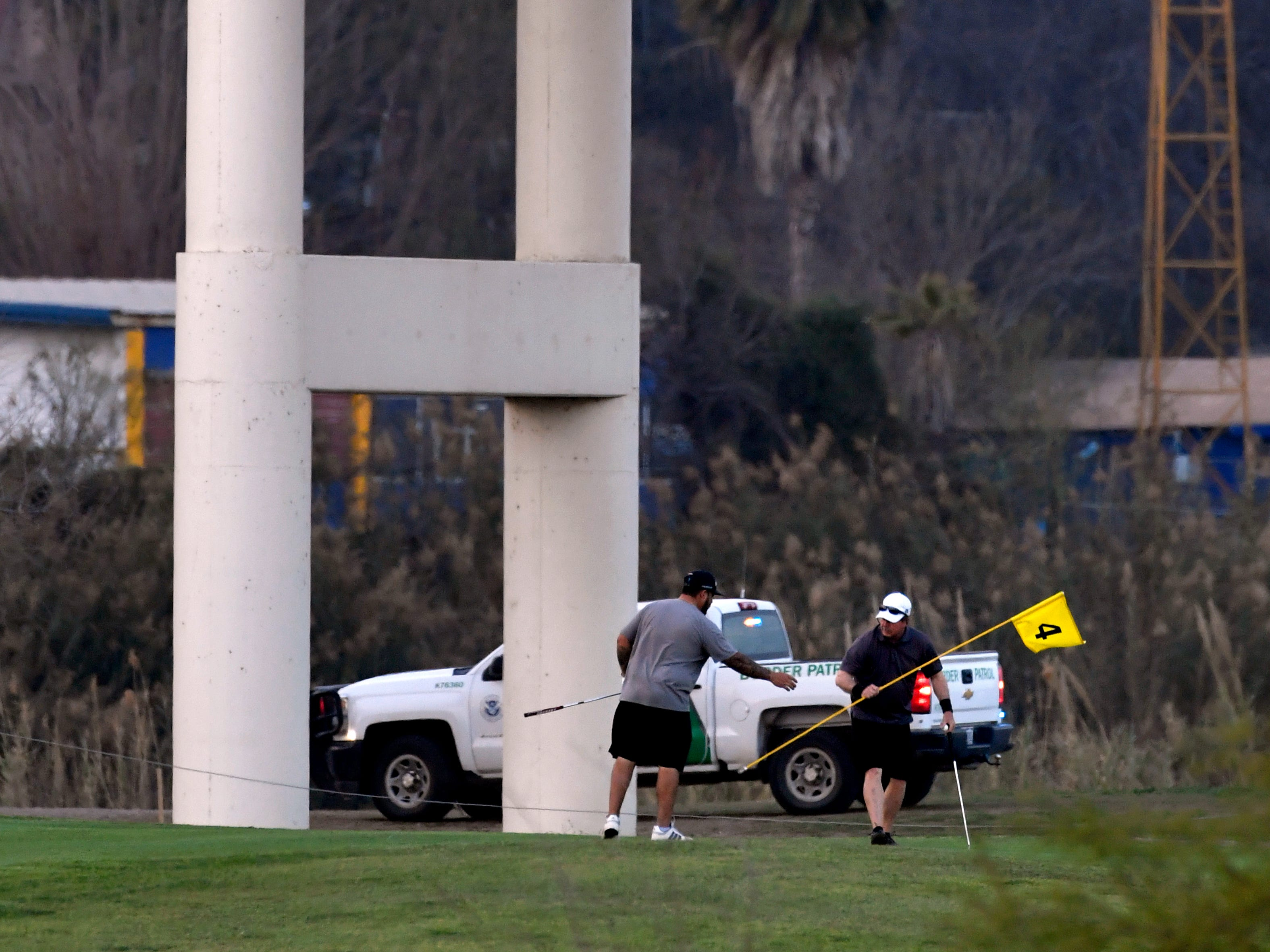 Golfers finish their round as border patrol vehicles parked above and below the Eagle Pass International Bridge Wednesday Feb. 6, 2019 guard against unauthorized entry. A caravan of Central American migrants has arrived in Piedras Negras and border law enforcement officials have increased their presence in response.