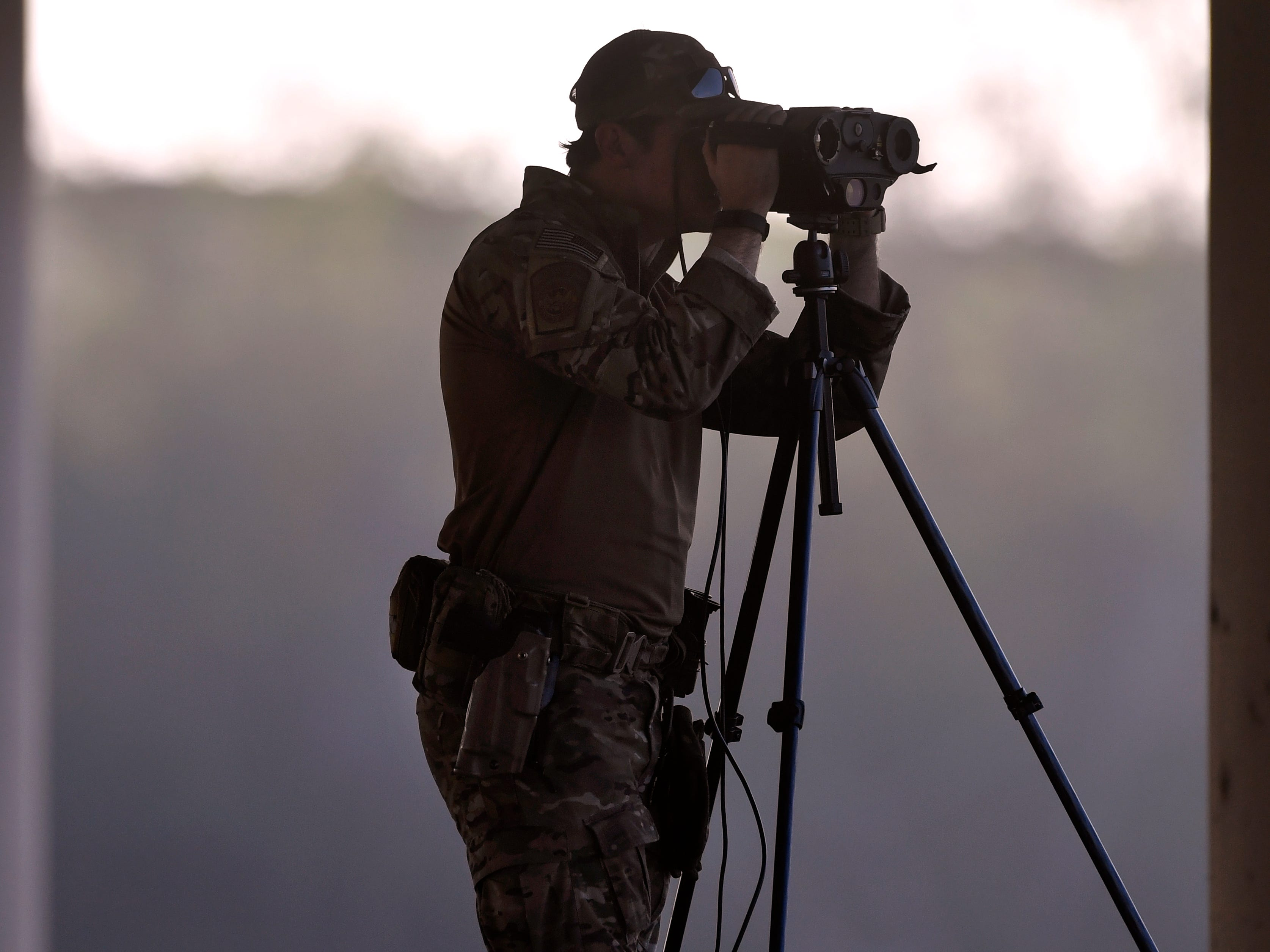 A U.S. Customs and Border Protection agent looks through binoculars while standing atop an armored vehicle beneath the Camino Real International Bridge in Eagle Pass Wednesday Feb. 6, 2019. A caravan of Central American migrants has arrived in Piedras Negras and border law enforcement officials have increased their presence in response.