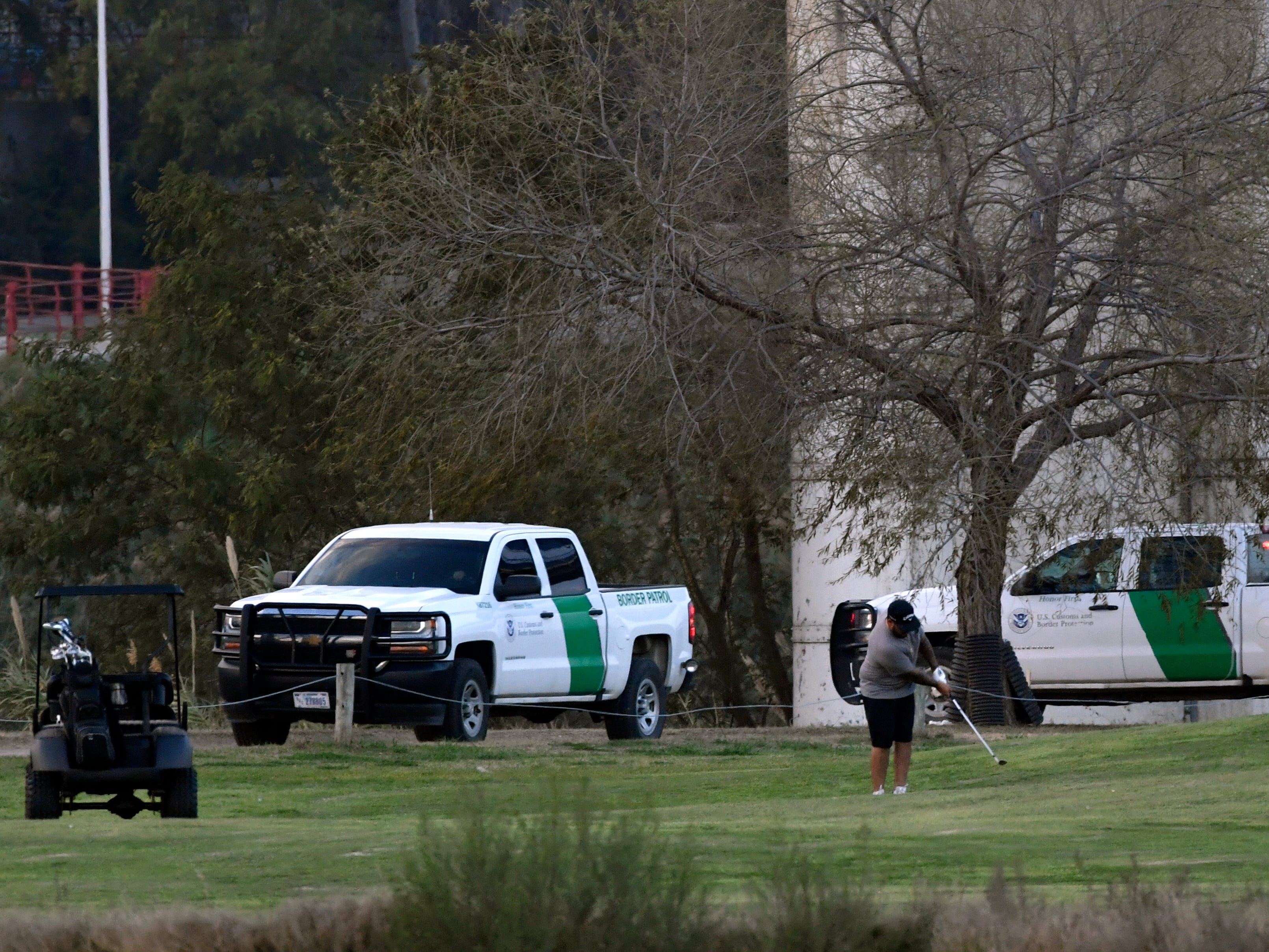 A golfer swings while border patrol vehicles stand guard beneath the Eagle Pass International Bridge Wednesday Feb. 6, 2019. A caravan of Central American migrants has arrived in Piedras Negras and border law enforcement officials have increased their presence in response.