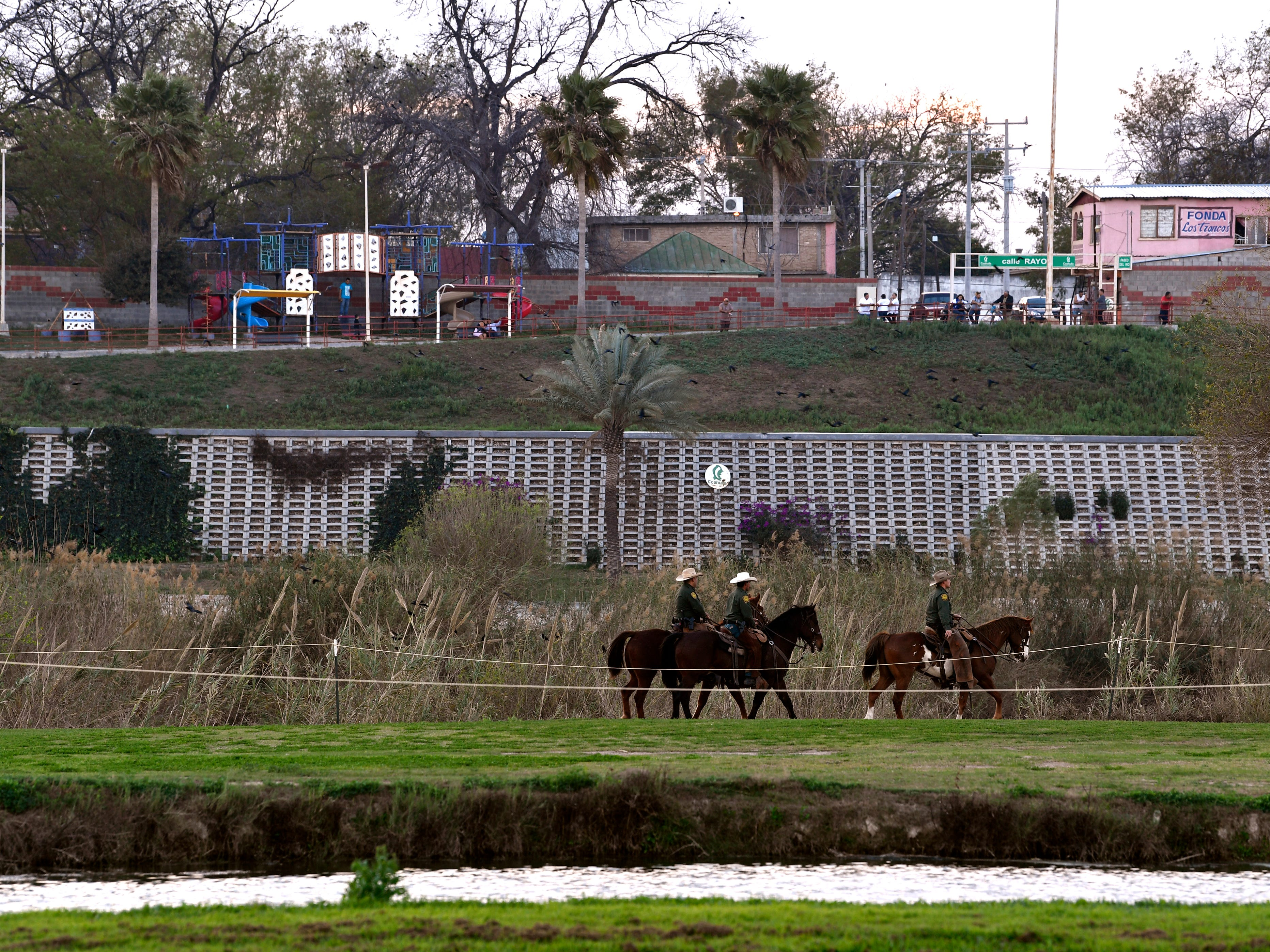 U.S. Customs and Border Protection agents ride horses Wednesday Feb. 6, 2019 along the Rio Grand between the two bridges connecting Eagle Pass to Piedras Negras. A caravan of Central American migrants has arrived in Piedras Negras and border law enforcement officials have increased their presence in response.