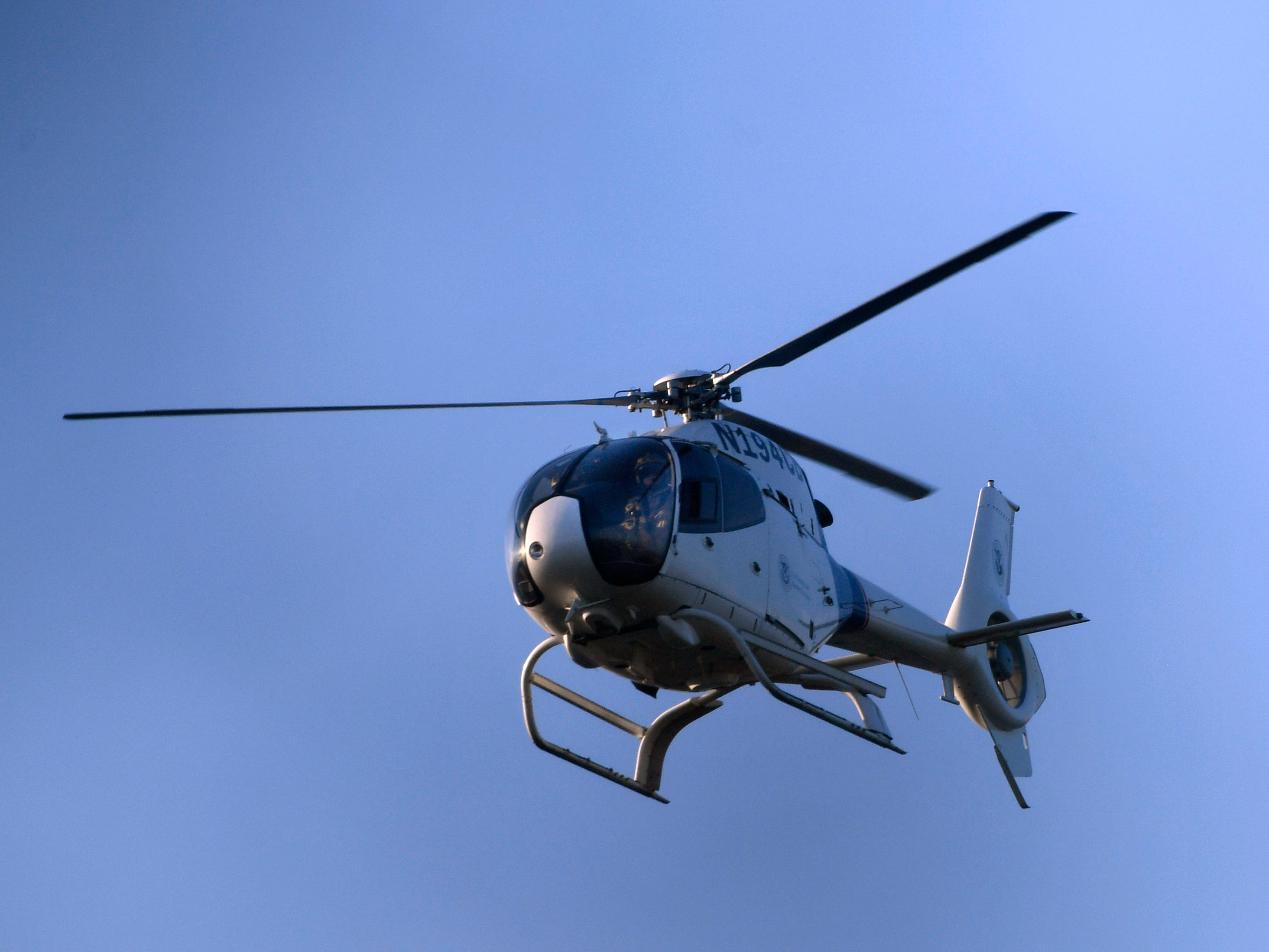 A U.S. Customs and Border Protection helicopter flies over the American side of the international border between Piedras Negras and Eagle Pass Wednesday Feb. 6, 2019. A caravan of Central American migrants has arrived in Piedras Negras and border law enforcement officials have increased their presence in response.