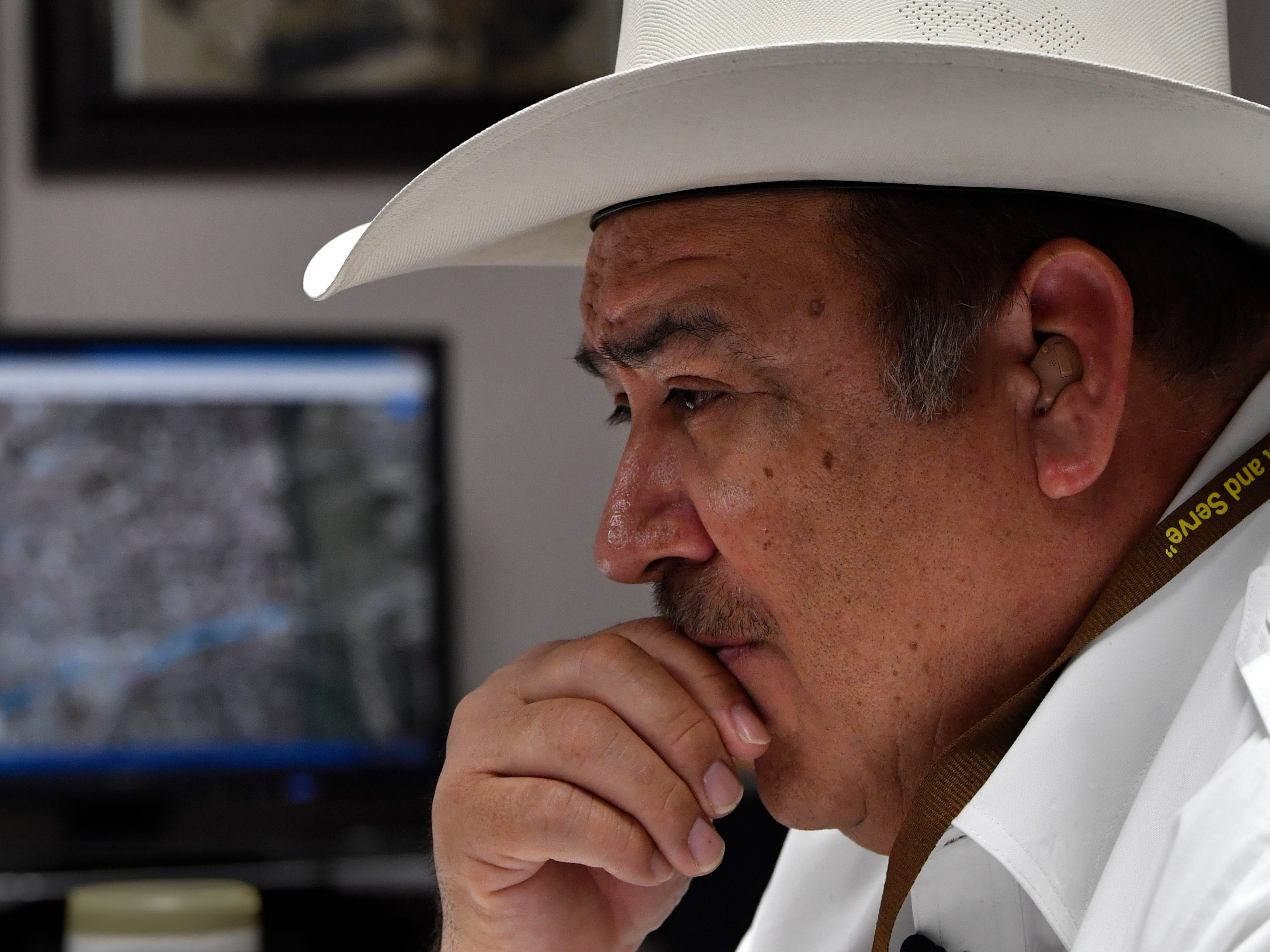 Maverick County Sheriff Tom Schmerber listens Wednesday Feb. 6, 2019 to a reporter's questions about the migrant caravan which has arrived in Piedras Negras.  A fifth generation Texan, the sheriff sits beneath a portrait of his German ancestor Joseph Schmerber who arrived in Texas during the Civil War.