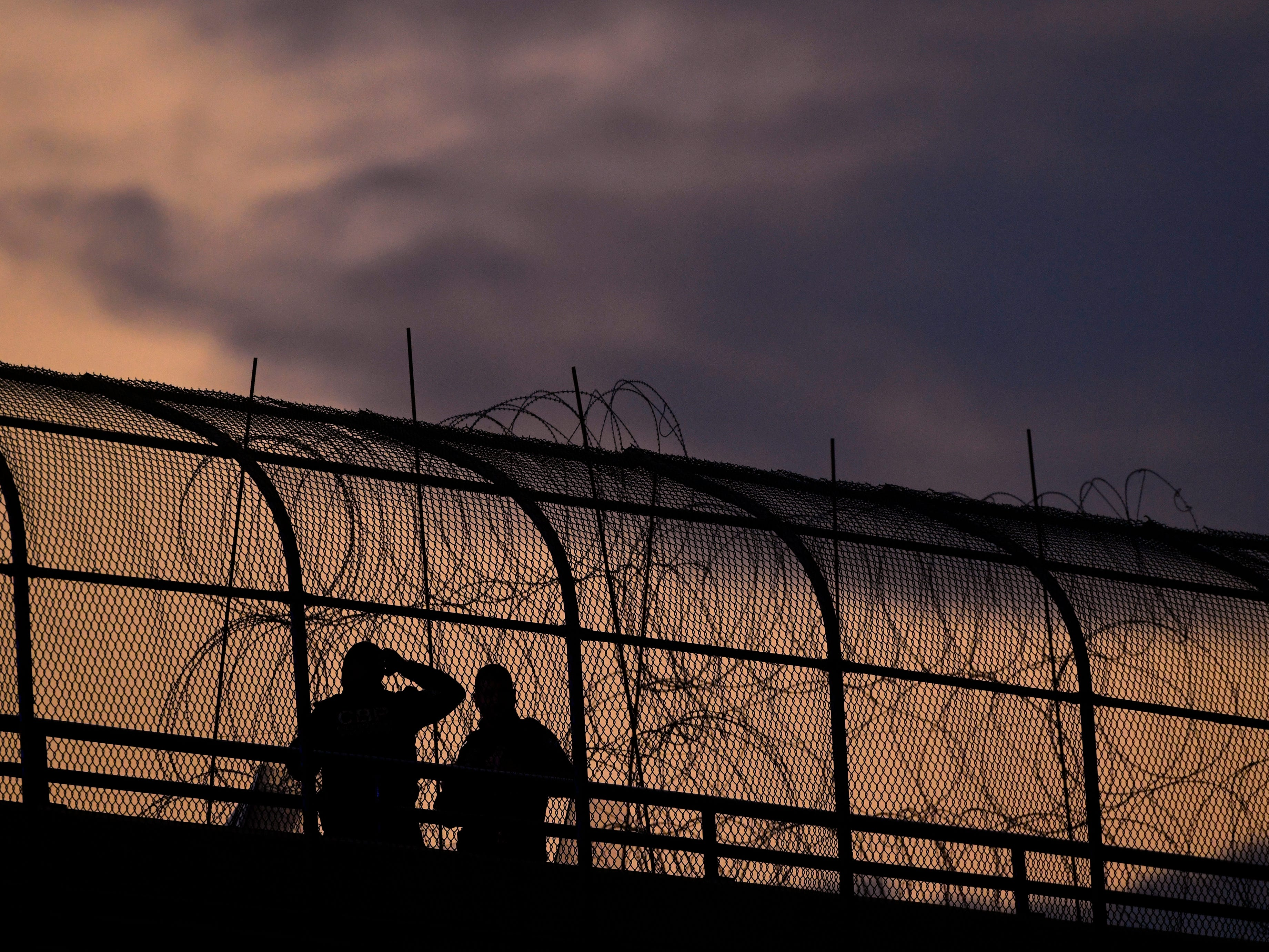 U.S. Customs and Border Protection agents are silhouetted against the evening sky Wednesday Feb. 6, 2019 on the Camino Real International Bridge in Eagle Pass.  caravan of Central American migrants has arrived in Piedras Negras and border law enforcement officials have increased their presence in response.
