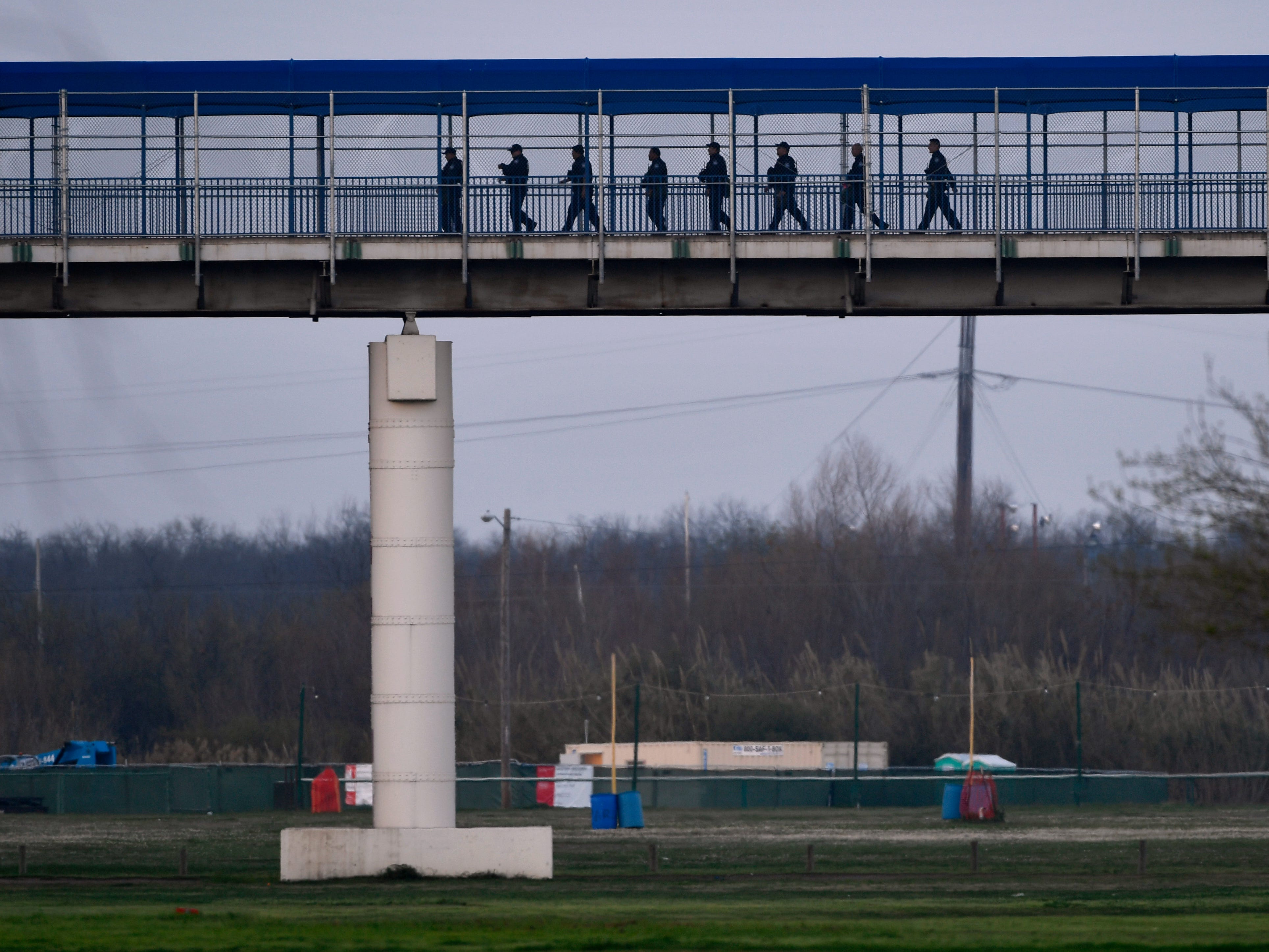 U.S. Customs and Border Protection agents walk to the checkpoint on the Eagle Pass International Bridge Wednesday Feb. 6, 2019. A caravan of Central American migrants has arrived in Piedras Negras and border law enforcement officials have increased their presence in response.