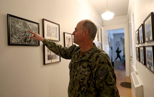 Rear Adm. Scott Gray, commander of Navy Region Northwest, looks over one of the many historical images that line a hallway in the 1896 historical house that his family lives in called Quarters C at Naval Base Kitsap Bremerton on Thursday.