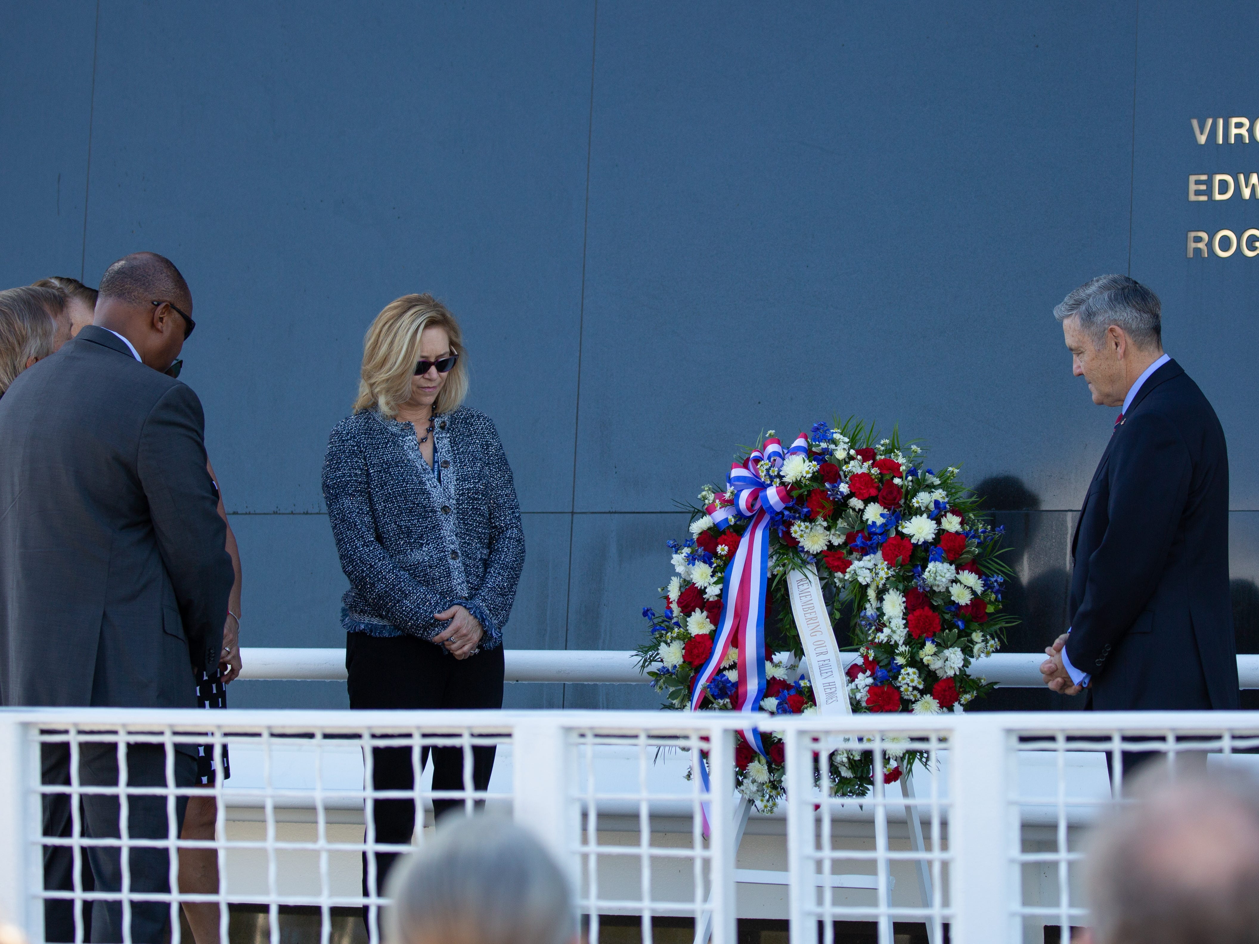 NASA officials stand silent to remember fallen astronauts at the Space Mirror Memorial for NASA's Day of Remembrance at the Kennedy Space Center Visitor Complex.
