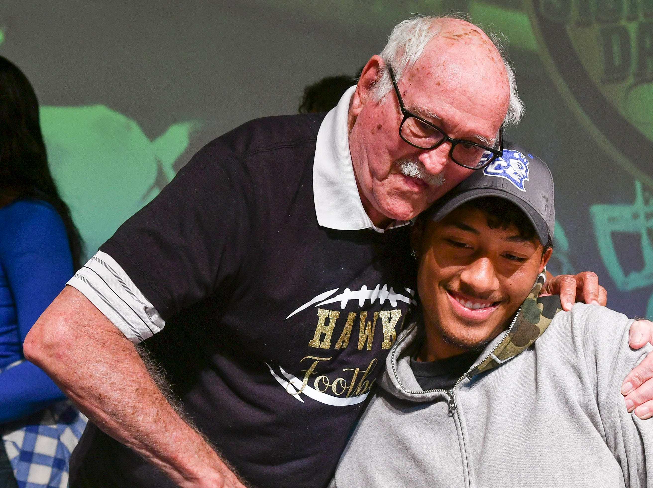 Viera High senior Shamaar Moore gets a congratulatory hug from family Wednesday during National Signing Day at the school.
