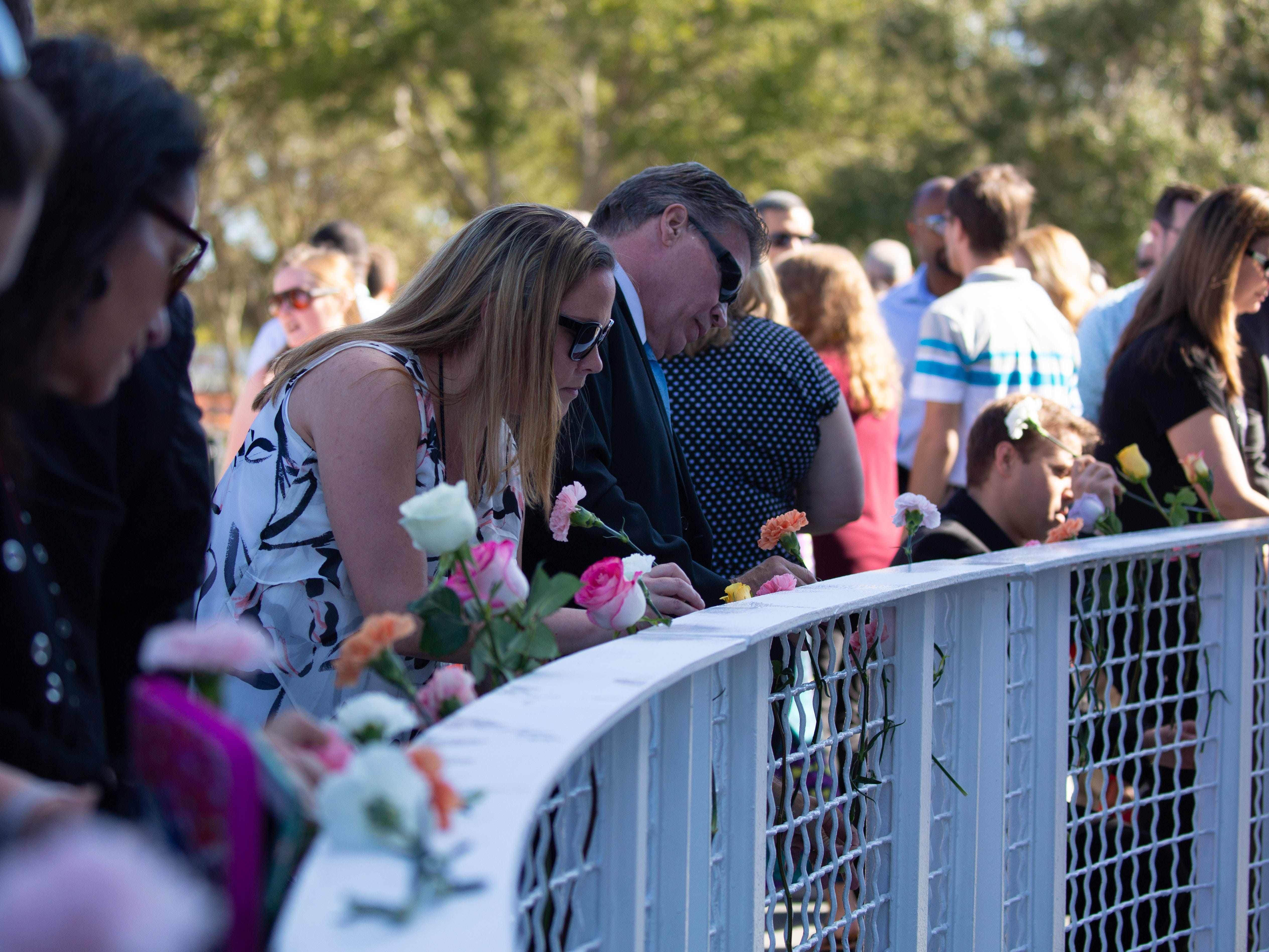Visitors lay flowers in front of the Space Mirror Memorial at the Kennedy Space Center Visitor Complex for NASA's Day of Remembrance on Thursday, Feb. 7, 2019.