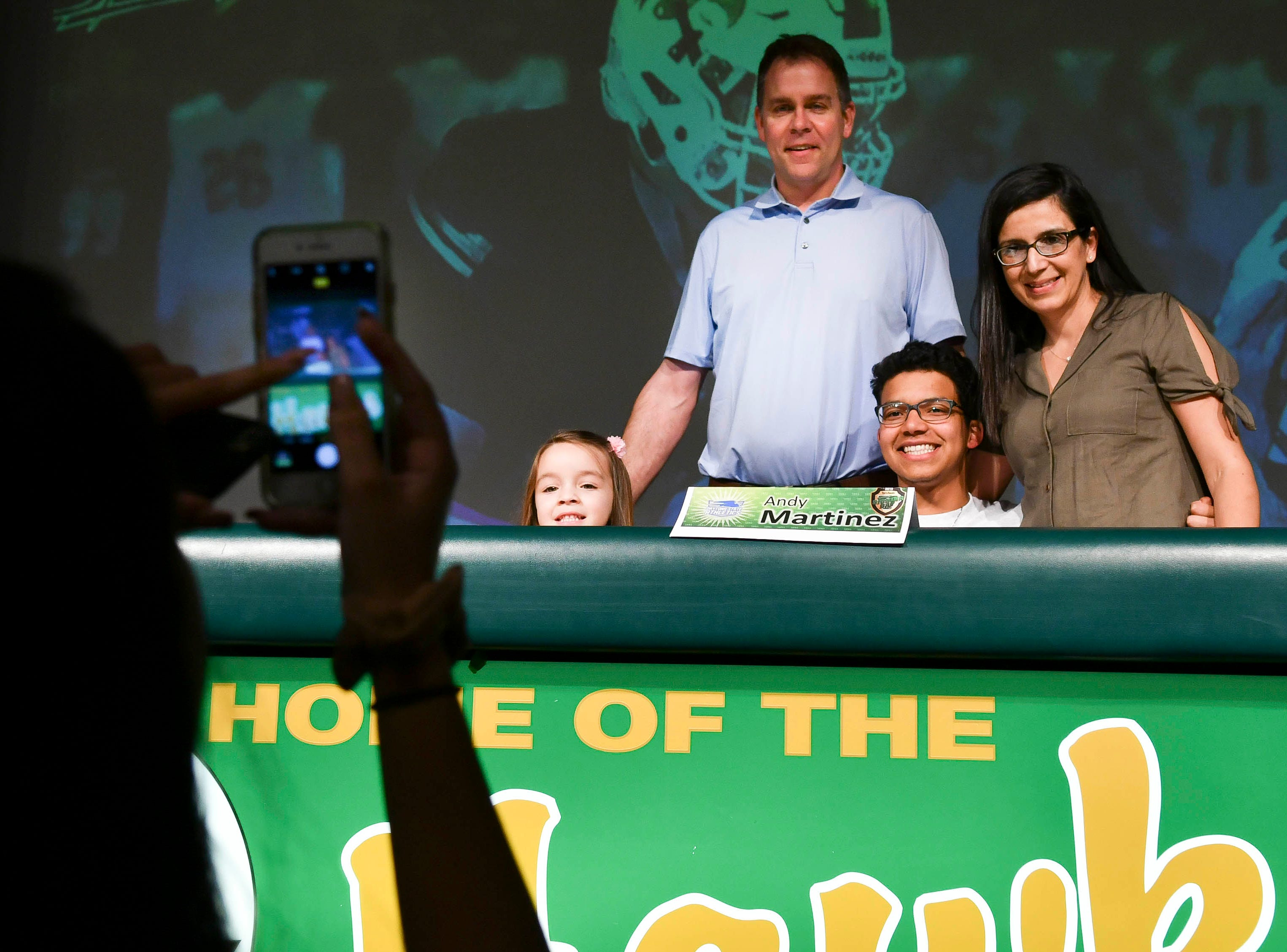 Viera High senior Andy Martinez has his photo taken with family Wednesday during National Signing Day at the school.