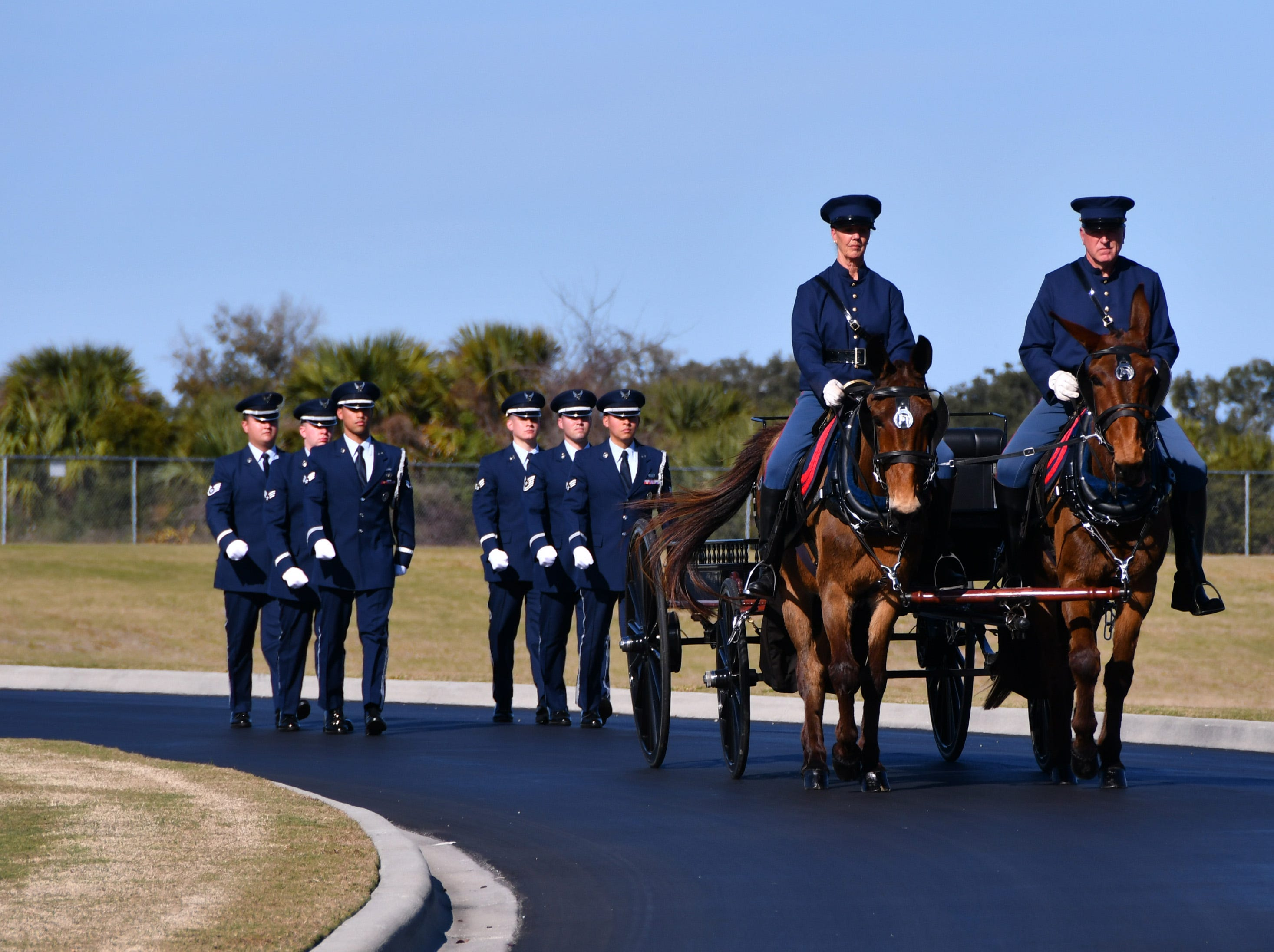 "The Patrick Air Force Base Honor Guard and caisson carrying the urns and folded flags approach the pavilion. A reburial ceremony was held at the Cape Canaveral National Cemetery Thursday afternoon for Flight Officer Edwin ""Eddie"" Cowan and his wife Theda with full military honors."