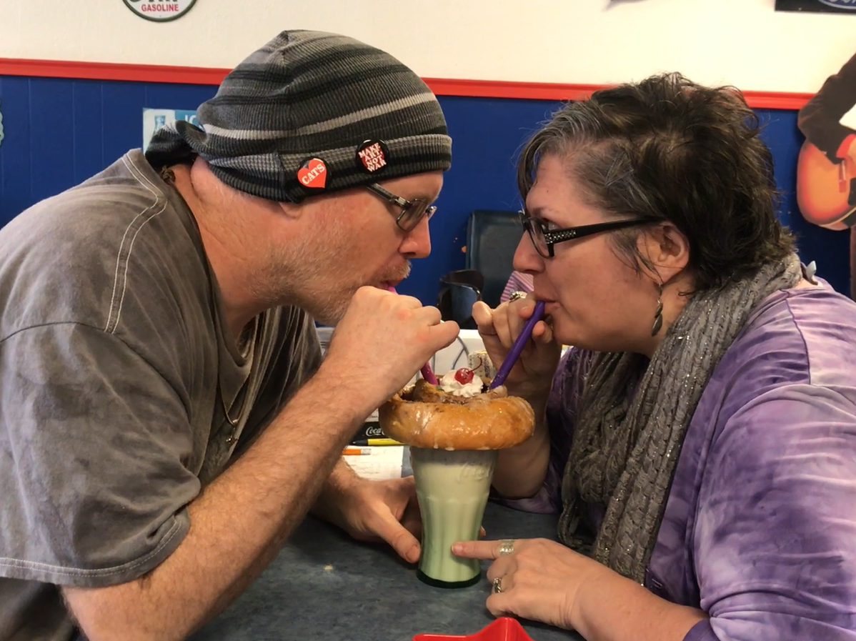 A couple enjoy the Area 51 malt shake at Sandi's Diner. The shake features a vanilla malt topped with a large cinnamon roll with whipped cream and a cherry on top.