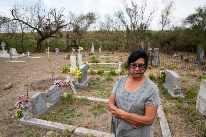 Yolanda Torres Castillo, 70, of Pharr, Texas, stands in the Eli Jackson Cemetery in San Juan, Texas where her parents and other family members are buried. Yolanda Torres Castillo came to visit the site on Wednesday, Feb. 6, 2019 after learning on the news that the soon-to-be-constructed border wall will be built on the levee bordering the cemetery, placing it on the Mexico side of the wall.