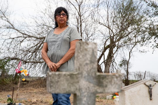 Yolanda Torres Castillo, 70, of Pharr, Texas, stands in front of her great-grandfather's grave at the Eli Jackson Cemetery in San Juan, Texas where her parents and other family members are buried. Yolanda Torres Castillo came to visit the site on Wednesday, Feb. 6, 2019 after learning on the news that the soon-to-be-constructed border wall will be built on the levee bordering the cemetery, placing it on the Mexico side of the wall.