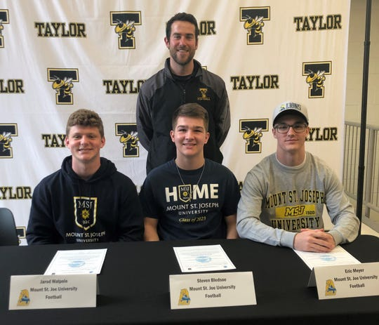 Taylor head football coach Mark Miller, back, joins his players who have agreed to play football for Mount St. Joseph University. They are, from left: Jarod Walpole, Steven Bledsoe and Eric Meyer.
