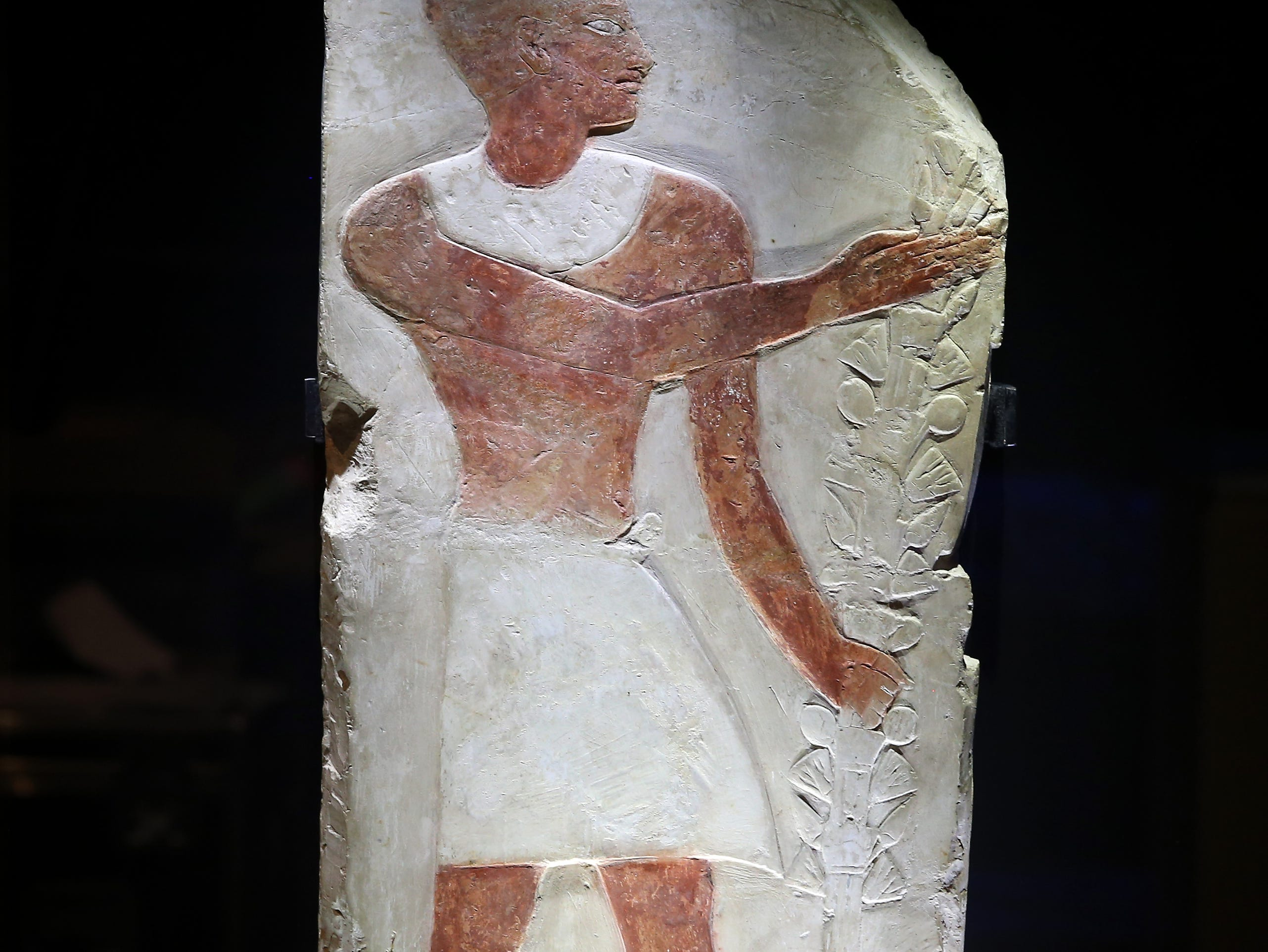 An ancient Egyptian relief, featuring a man with a festive bouquet, is uncrated for display, Thursday, Feb. 7, 2019, at Cincinnati Museum Center in Cincinnati. The relief is made of limestone and is about 3,500 years old.