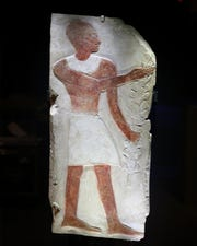An ancient Egyptian relief, featuring a man with a festive bouquet, is uncrated for display.