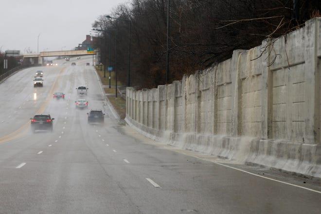 Rushing water and debris flows into westbound Columbia Parkway just east of downtown below the Mt. Adams neighborhood of Cincinnati on Thursday, Feb. 7, 2019.
