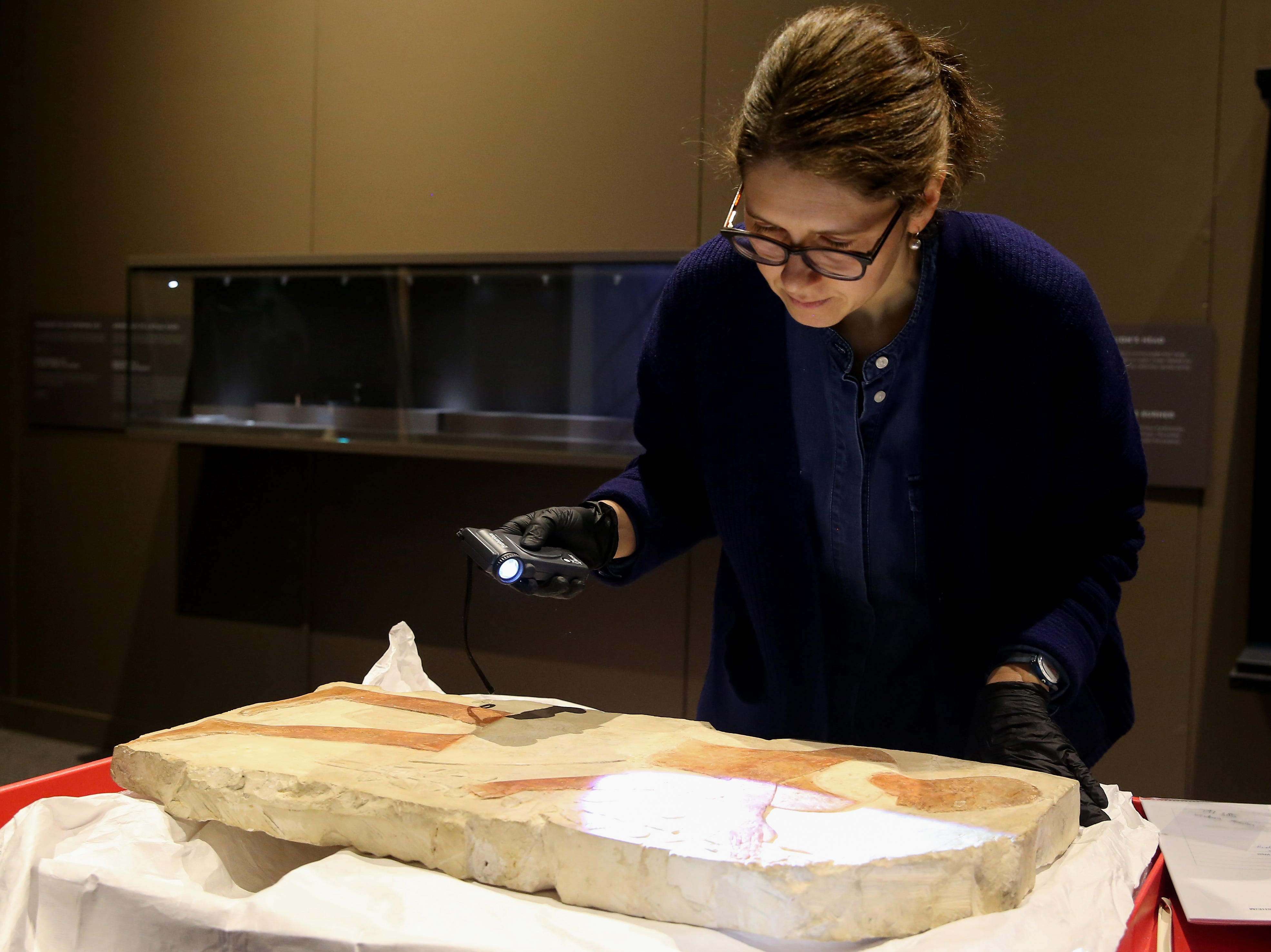 Conservator Claudia Schindler inspects an ancient Egyptian relief, featuring a man with a festive bouquet as it is uncrated for display, Thursday, Feb. 7, 2019, at Cincinnati Museum Center in Cincinnati. The relief is made of limestone and is about 3,500 years old.