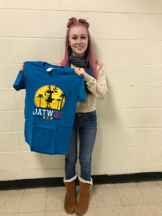 """Graphic Communications student Mesara Scarpellino of South Bound Brook shows off her tee-shirt design used at the 10th Annual """"Jingle All The Way 3K"""" festive holiday run this past December."""