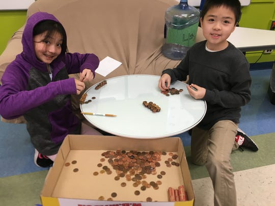 Angelina Huang and Alexander Cai, grade 5 students, counting pennies.