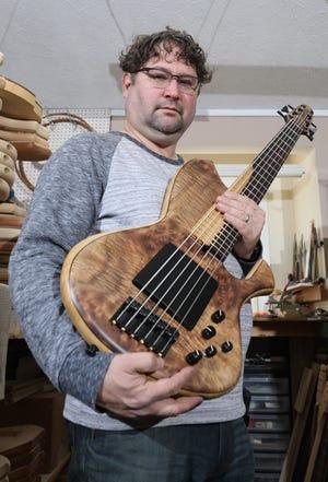 Pete Skjold, owner of Skjold Design Guitars, holds one of his offerings in his Warsaw workshop. Skjod hand makes custom bass guitars.