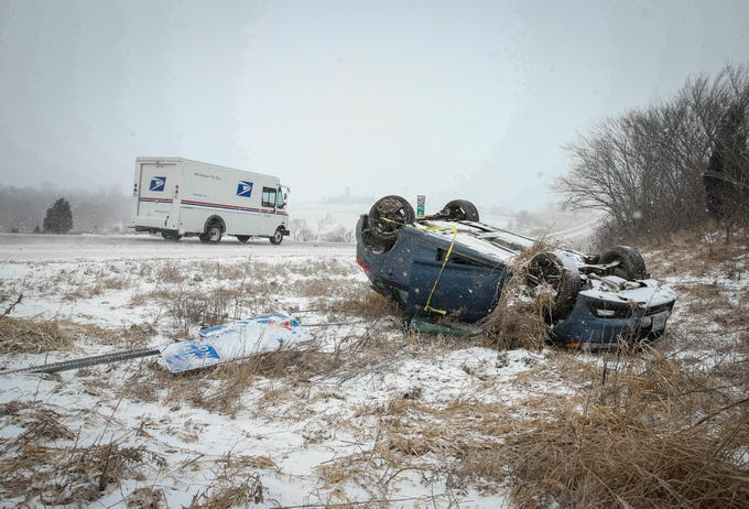 A United States Postal Service truck drives by a car that rolled over along Highway 65 outside of Indianola as blowing snow and freezing rain caused travel concerns during another round of winter weather on Thursday, Feb. 7, 2019.