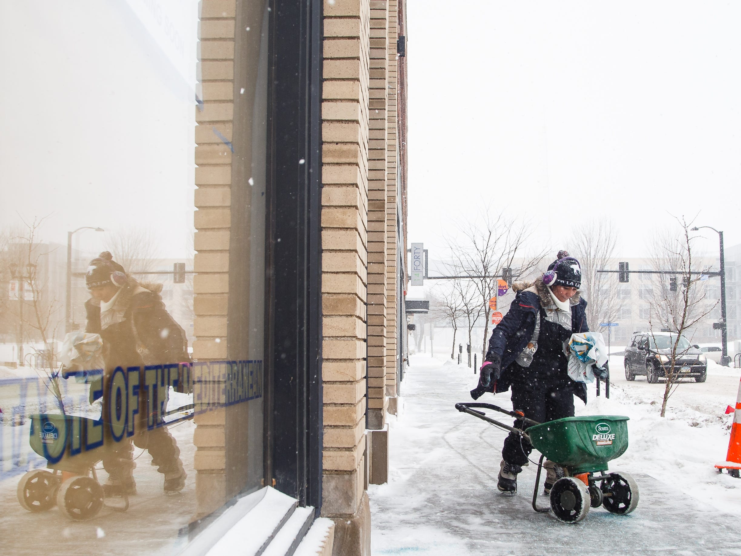 Betty Lopez spreads salt on a sidewalk as another round of snow falls in Des Moines on Thursday, Feb. 7, 2019.