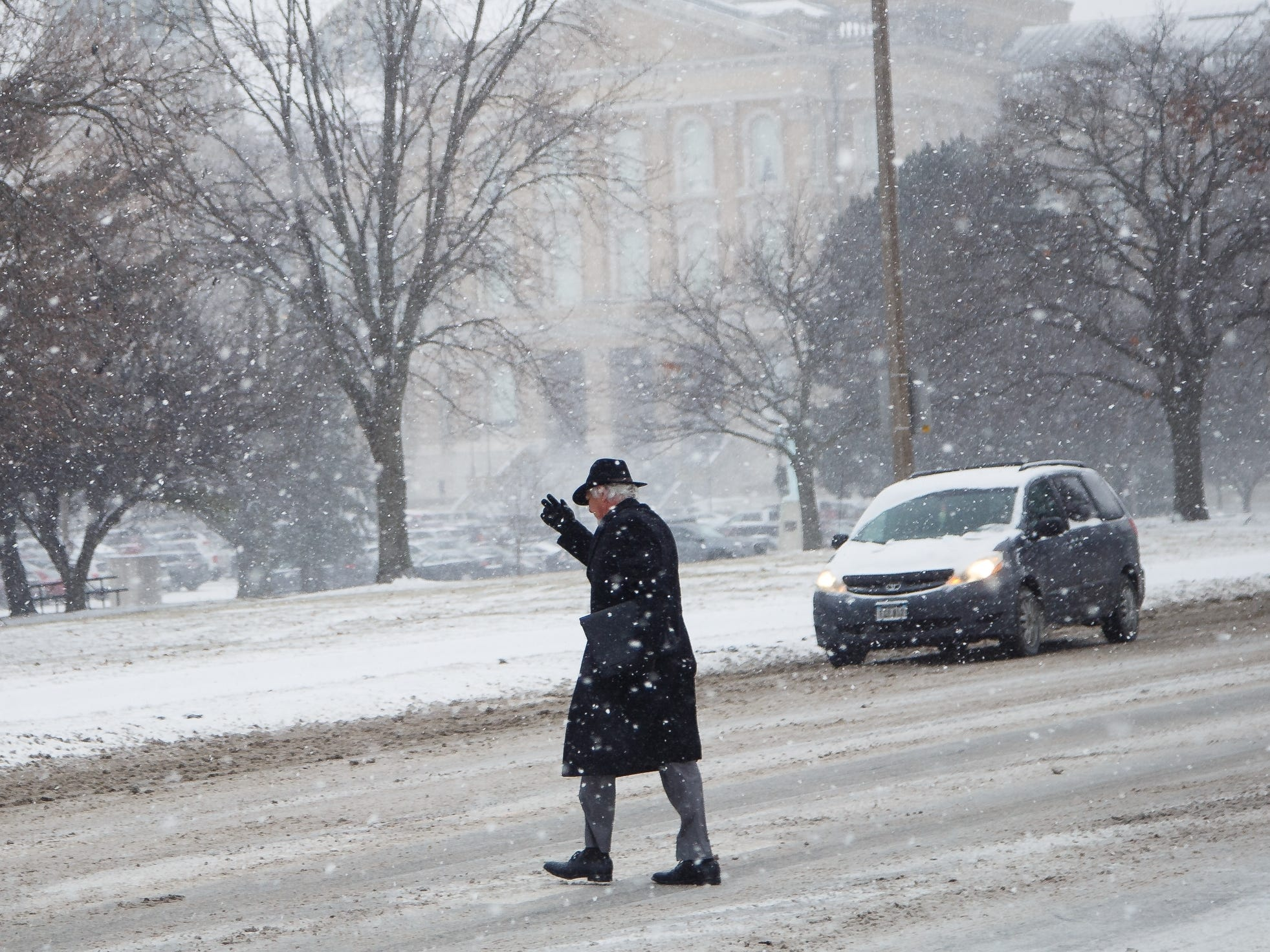A man crosses the street in front of the state capitol as another round of snow falls in Des Moines on Thursday, Feb. 7, 2019, in Des Moines.