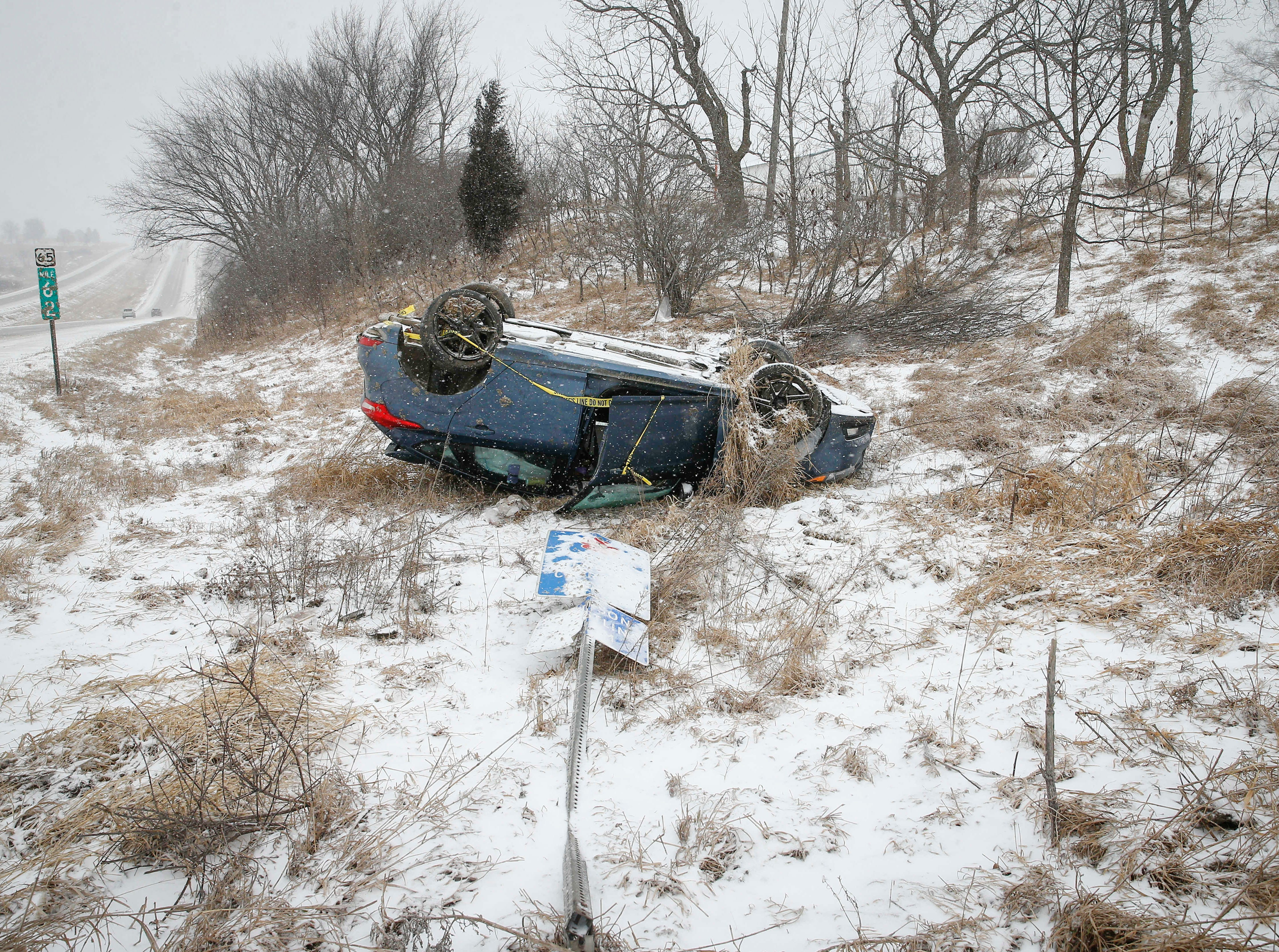 A car sits on its hood along Highway 65 outside of Indianola as strong wind gusts and freezing drizzle caused travel issues during another round of winter weather on Thursday, Feb. 7, 2019.