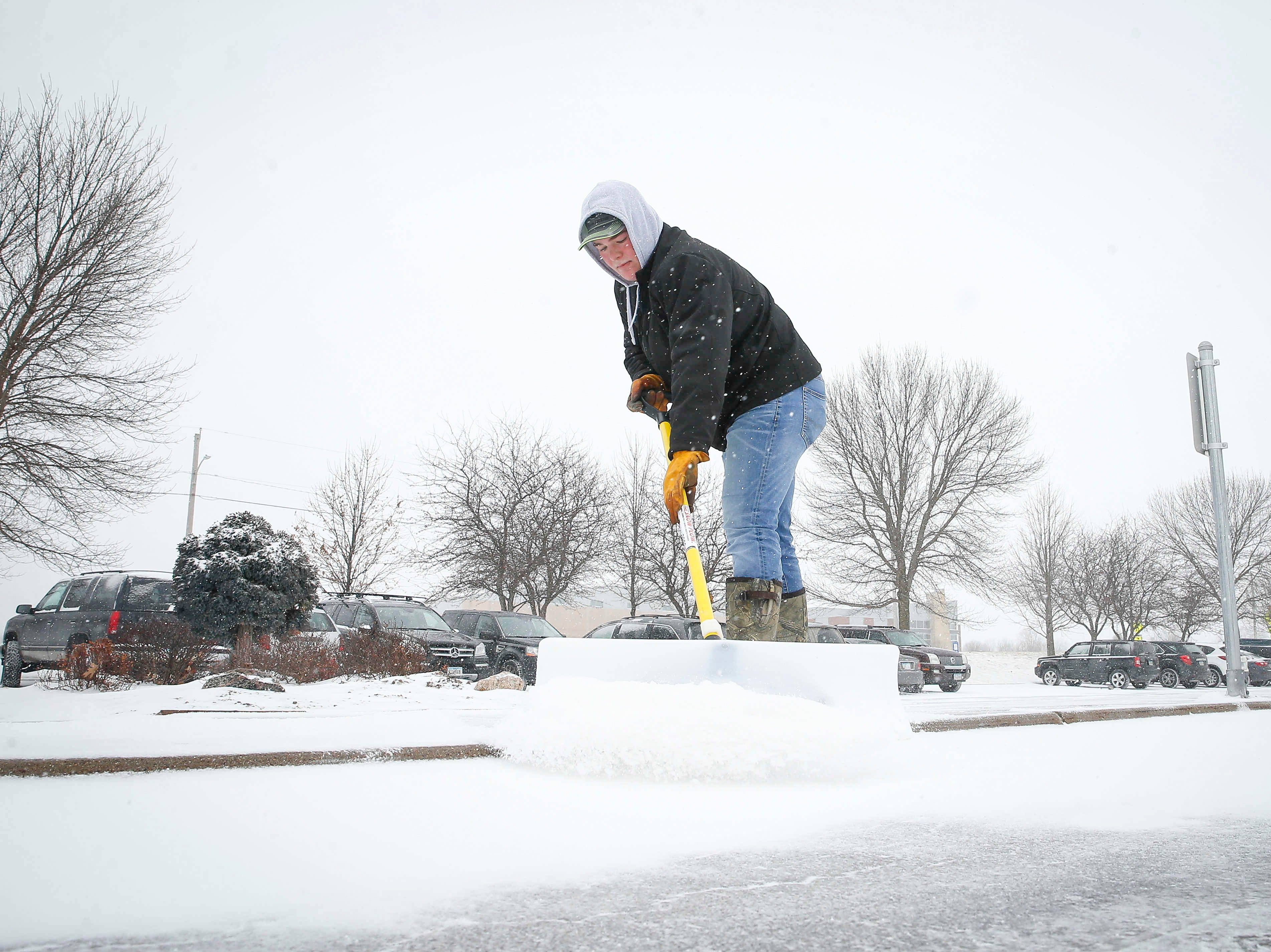 Ethan Clark of Norwalk shovels a sidewalk at Valley Church in West Des Moines as a new round of winter weather fell across parts of central Iowa on Thursday, Feb. 7, 2019.