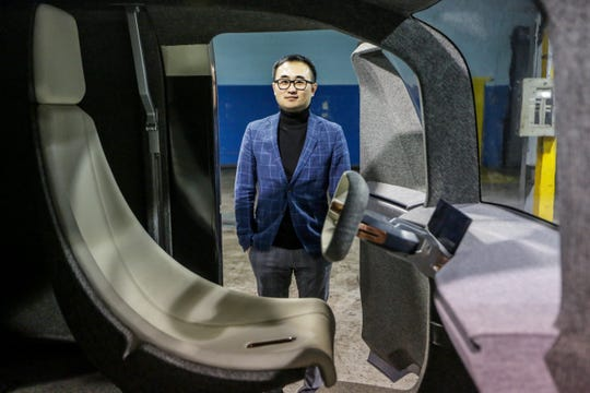 """Mike Tianye Wang, CEO and Board Chairman of Quadrobot, stands in a warehouse where the """"UP"""" package delivery truck is housed in Madison Heights, Mich. photographed on Thursday, Feb. 5, 2019."""